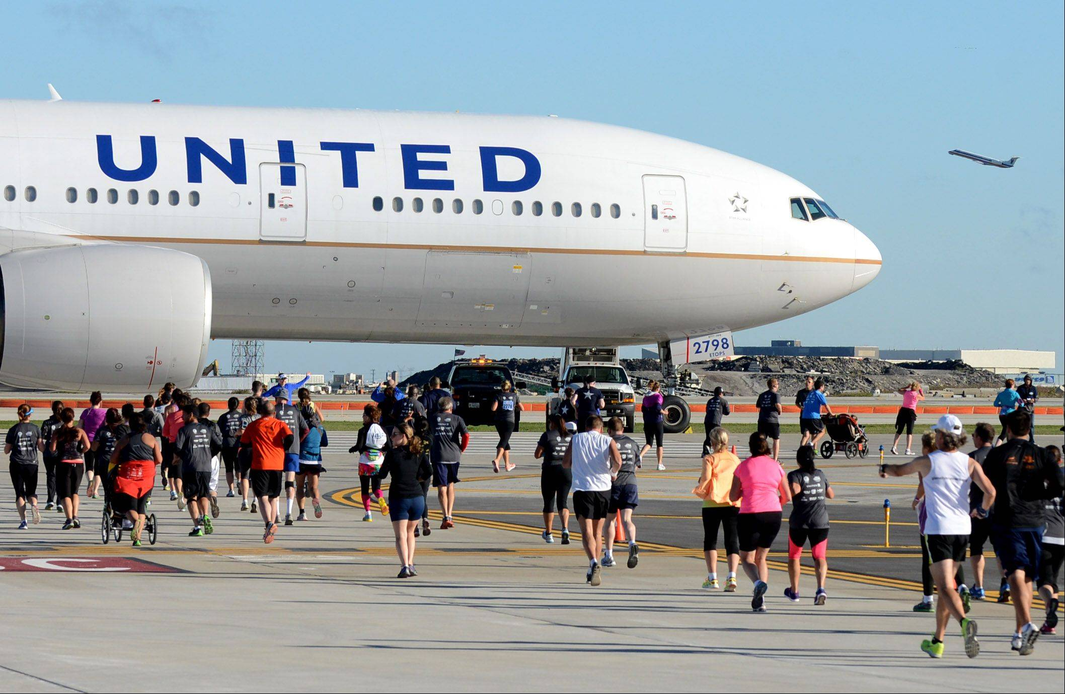 "Runners approach a parked Boeing 777 on their route during Sunday's ""Run on the Runway"" 5K and 10K runs at O'Hare International Airport. The races took place on new runway 10C-28C before it opens to air traffic Oct. 17. Proceeds from the event benefit the Wounded Warrior Project."