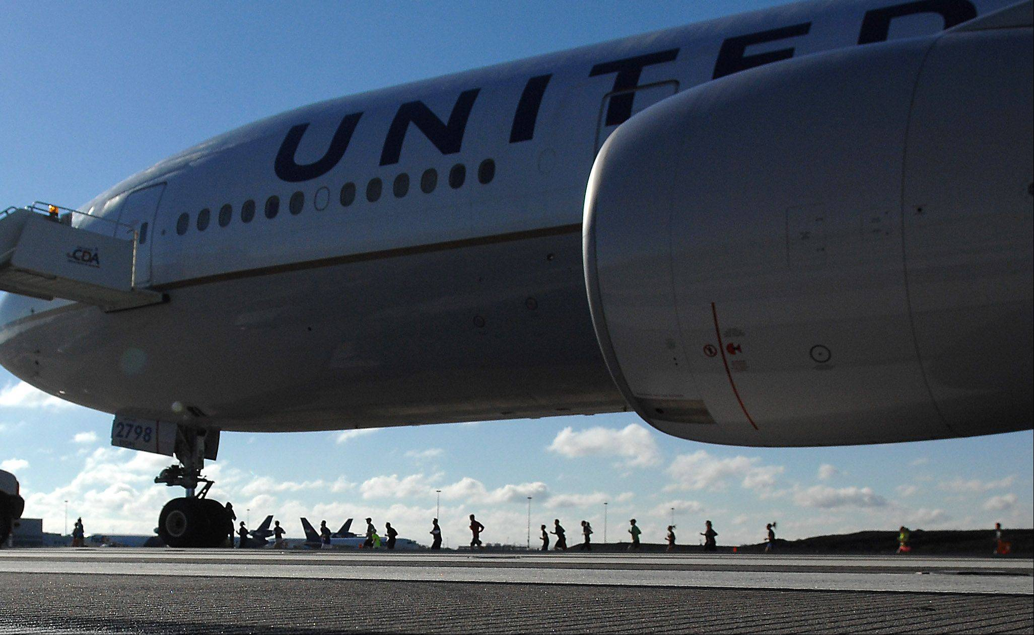 "A United Arlines Boeing 777 dwarfs runners as they make the turn on the new O'Hare International Airport runway ""Run on the Runway"" 5K and 10K runs Sunday. The new runway opens to air traffic Oct. 17."