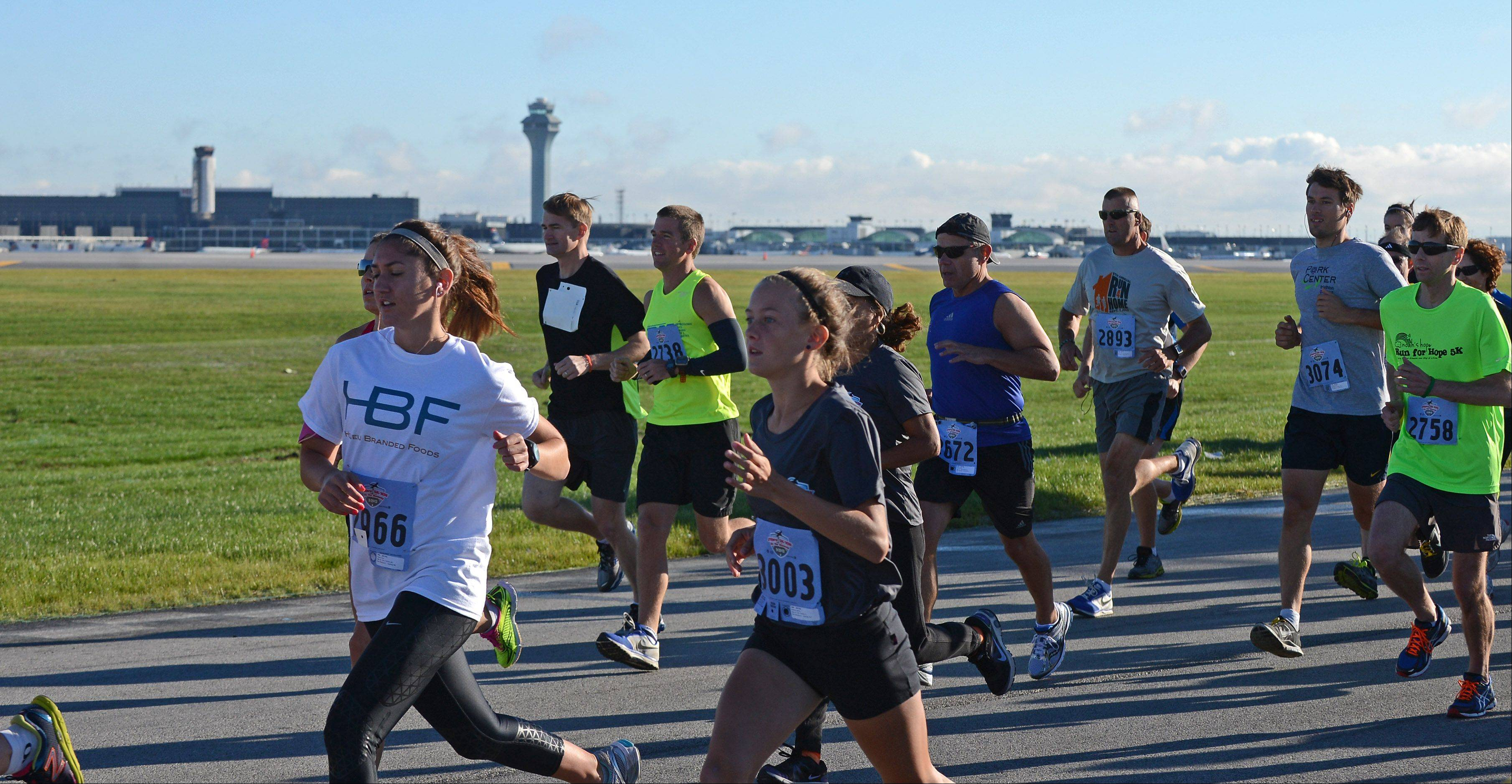 "10K runners take off at the start of the ""Run on the Runway"" 5K and 10K races Sunday at O'Hare International Airport. The course took participants onto new runway 10C-28C before it opens to air traffic Oct. 17. Proceeds from the event will benefit the Wounded Warrior Project."