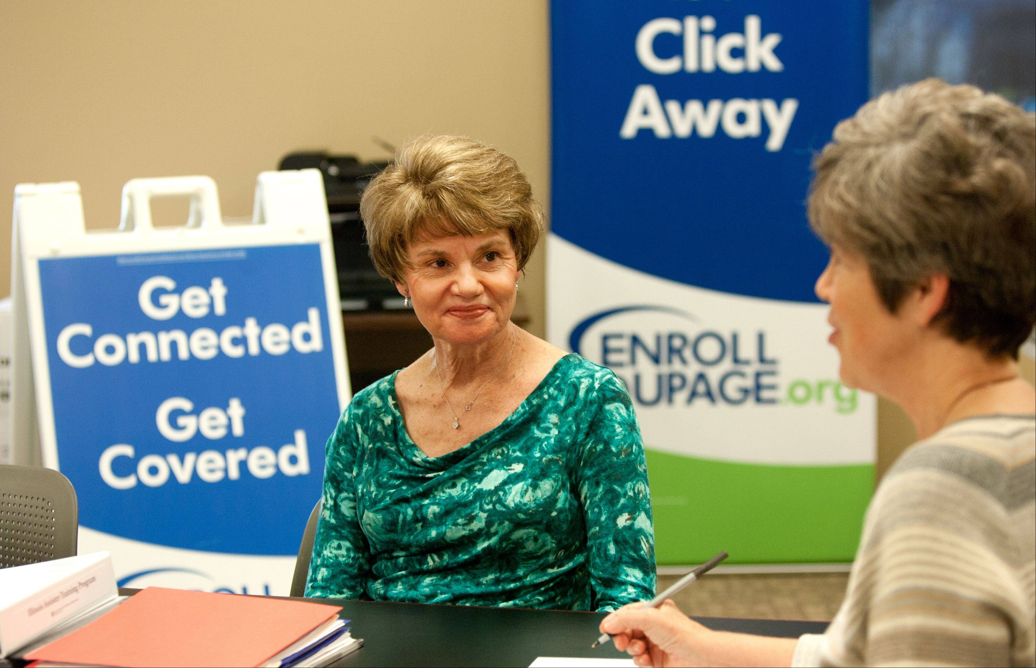 Margie Tarpey, Enroll DuPage program coordinator, left, listens to Jane Macdonald, director of client engagement, as she speaks with a handful of volunteers in training. The meeting at Loaves & Fishes in Naperville occurred to help implement the Affordable Care Act in DuPage County.