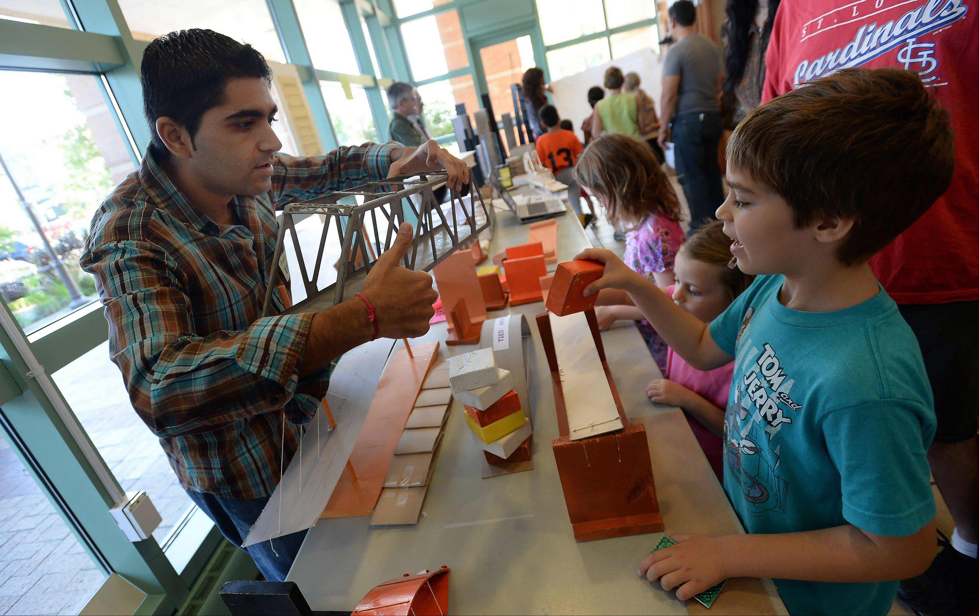 Sapan Trivedi of Schaumburg, a member of the Structural Engineers Association of Illinois, explains the design of a bridge to Teodor Djuric, 6, of Des Plaines at the fifth annual Family Science Expo, held Saturday at the Des Plaines Public Library.