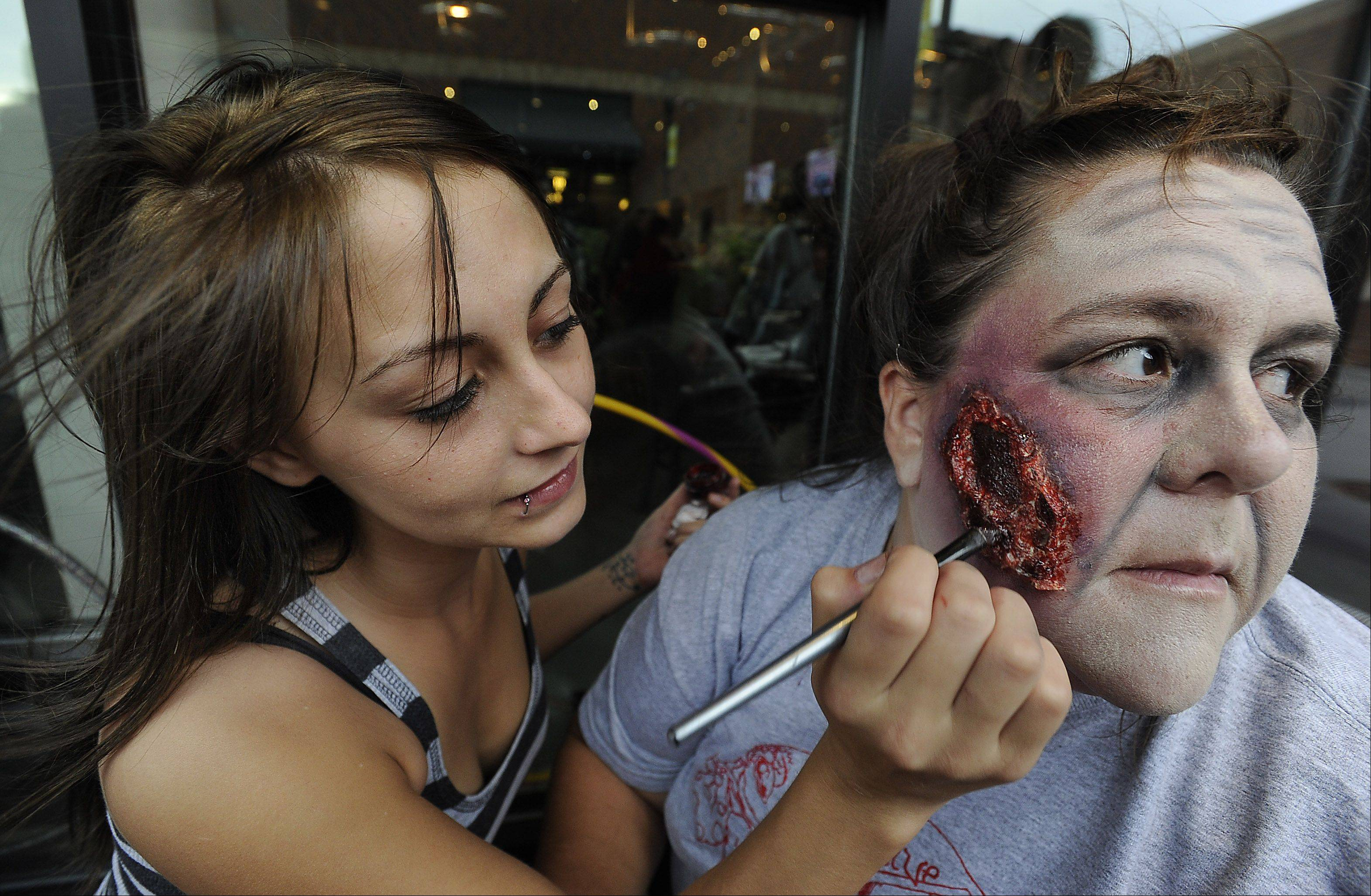 Artist Julie Goza of McHenry applies fake blood effects on the face of Pam Blake of Fox Lake Saturday for the Save the Brains Zombie Crawl to Fight ALS at Randhurst Village in Mount Prospect.
