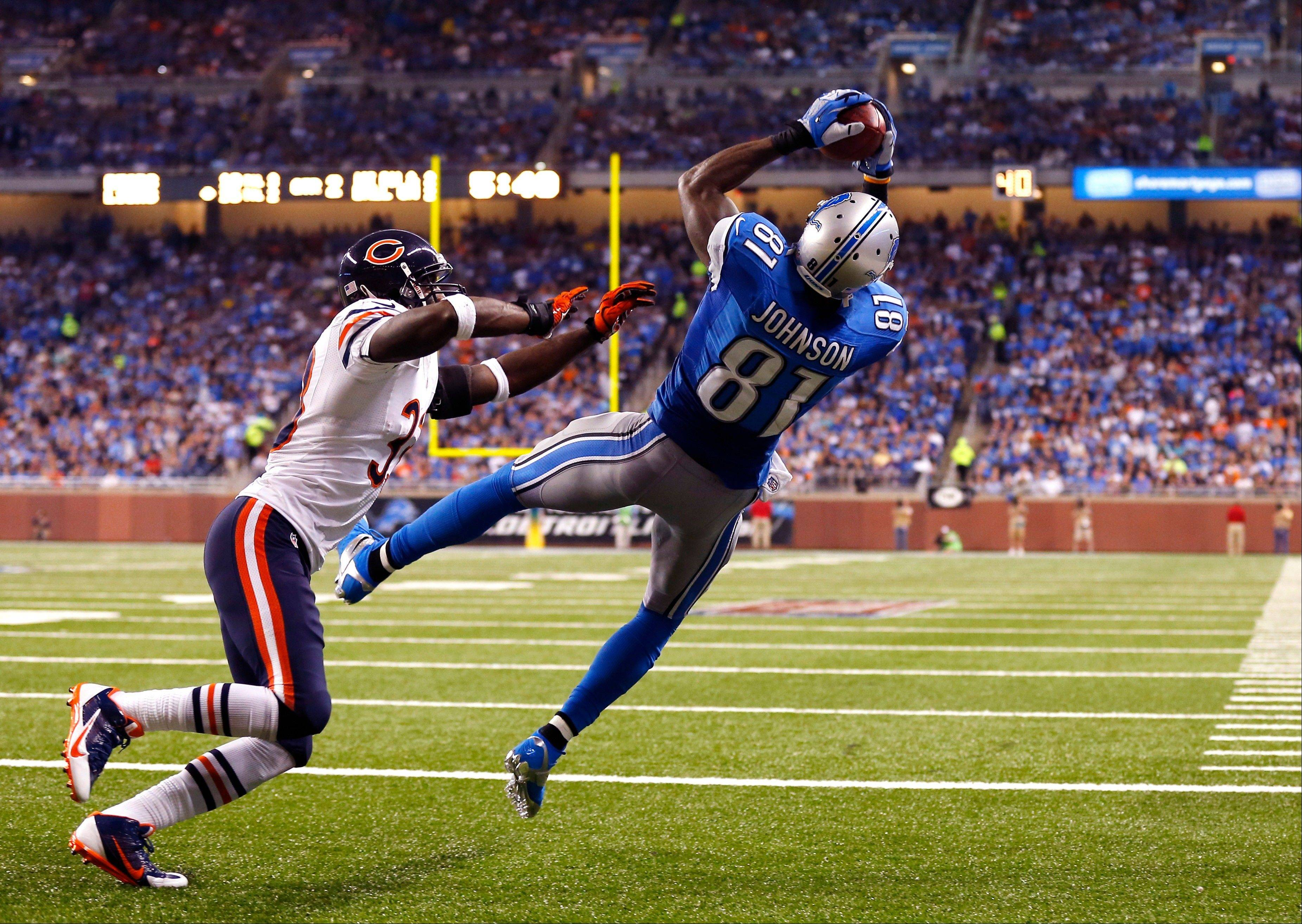 Detroit Lions wide receiver Calvin Johnson (81), defended by Chicago Bears cornerback Charles Tillman (33), catches a two-yard touchdown from quarterback Matthew Stafford during the second quarter.
