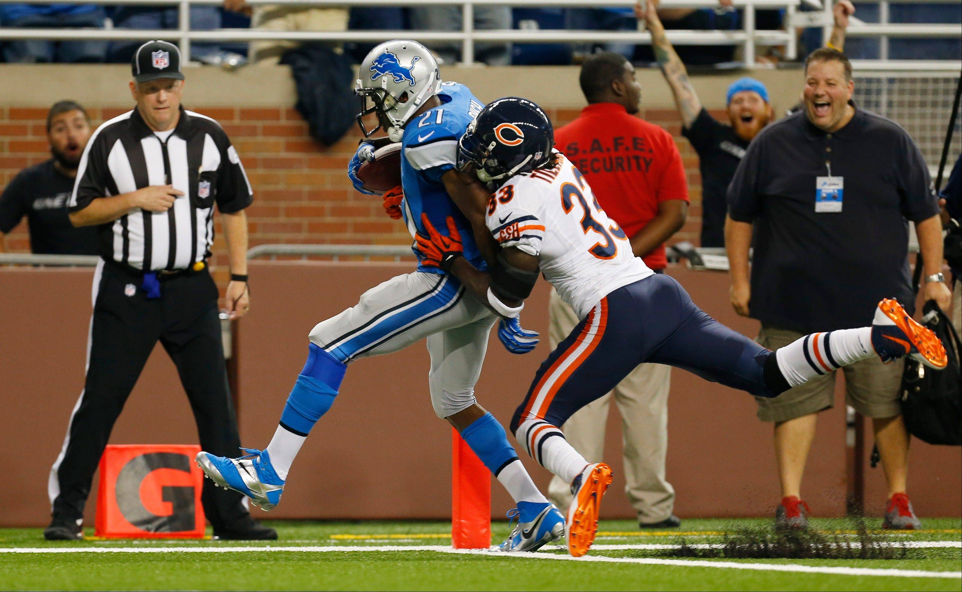Detroit Lions running back Reggie Bush (21), defended by Chicago Bears cornerback Charles Tillman (33) scores on a 37-yard touchdown run during the second quarter.