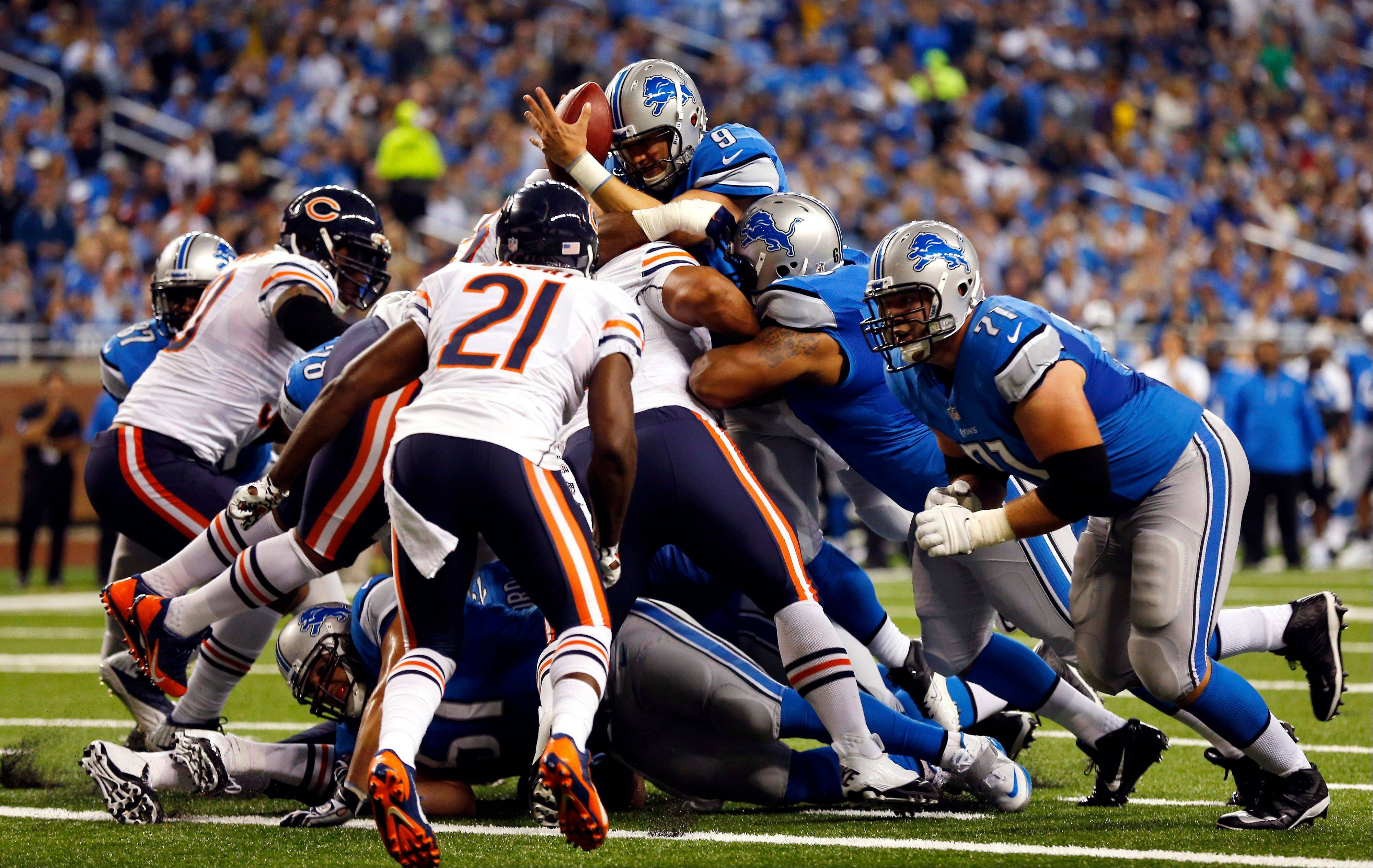 Detroit Lions quarterback Matthew Stafford (9) goes over the center for a touchdown but loses control of the ball during the second quarter.