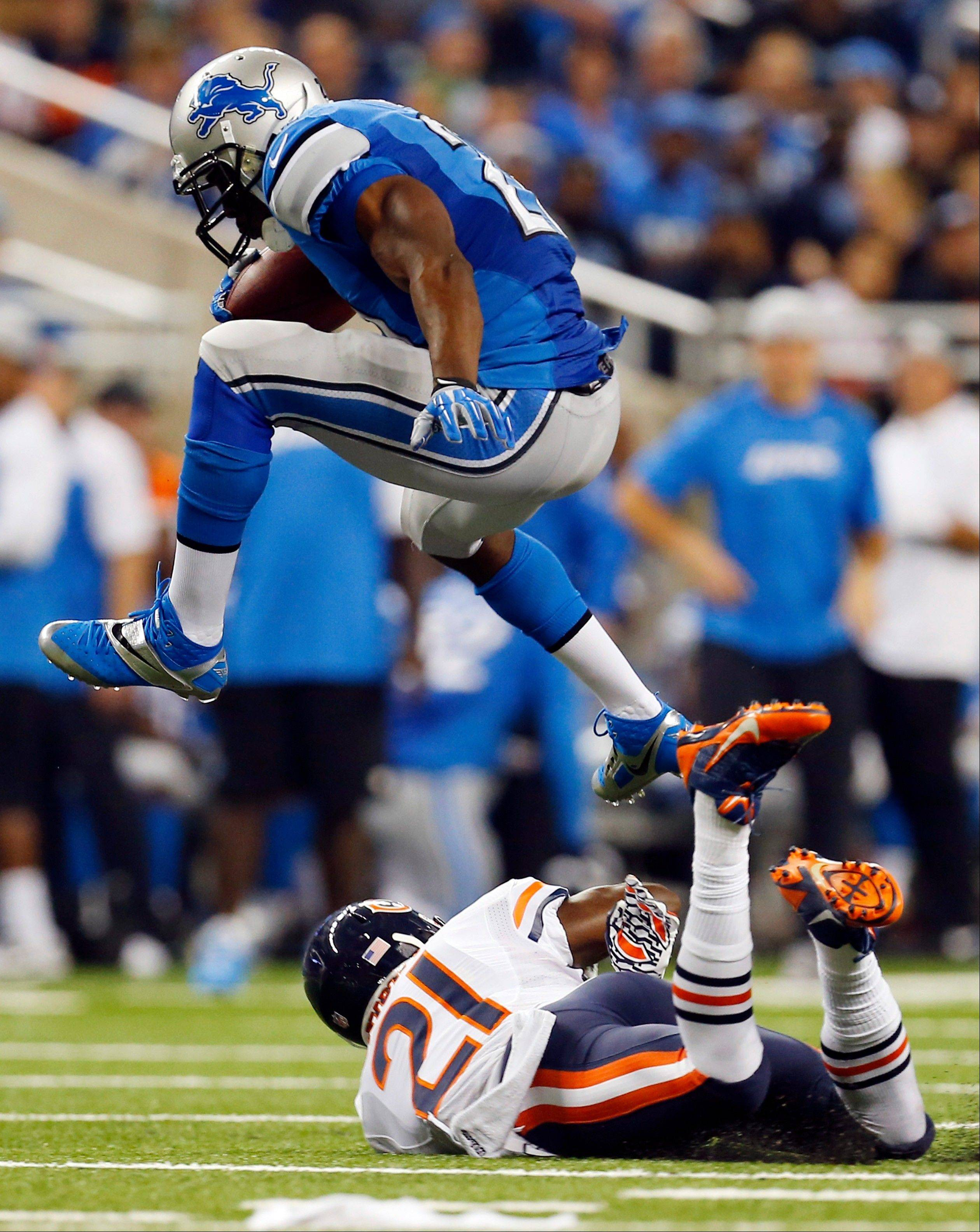 Detroit Lions running back Reggie Bush, top, jumps over Chicago Bears strong safety Major Wright (21) while heading for the end zone on a 37-yard touchdown run during the second quarter.