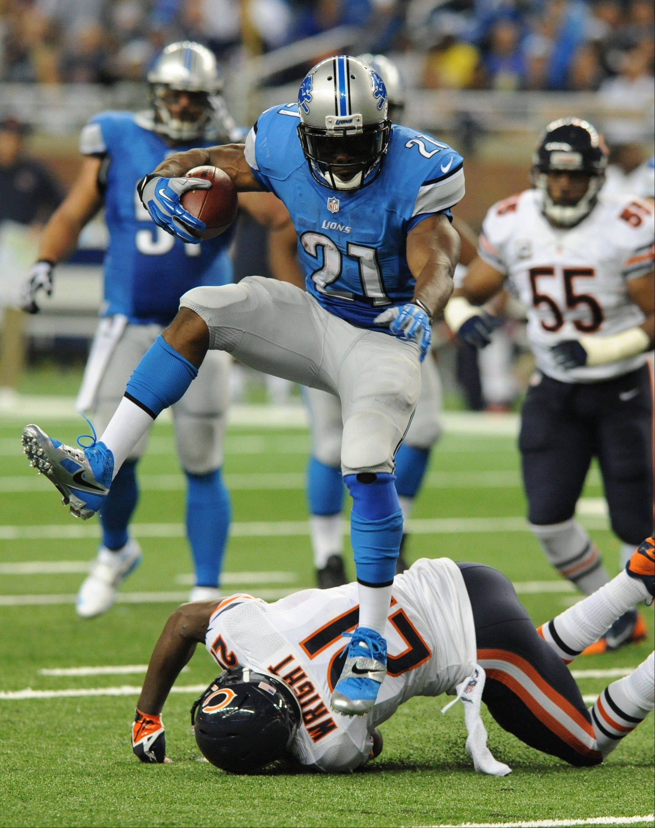 Detroit Lions running back Reggie Bush (21) jumps over Chicago Bears strong safety Major Wright (21) as he runs for a 37-yard touchdown during the second quarter.