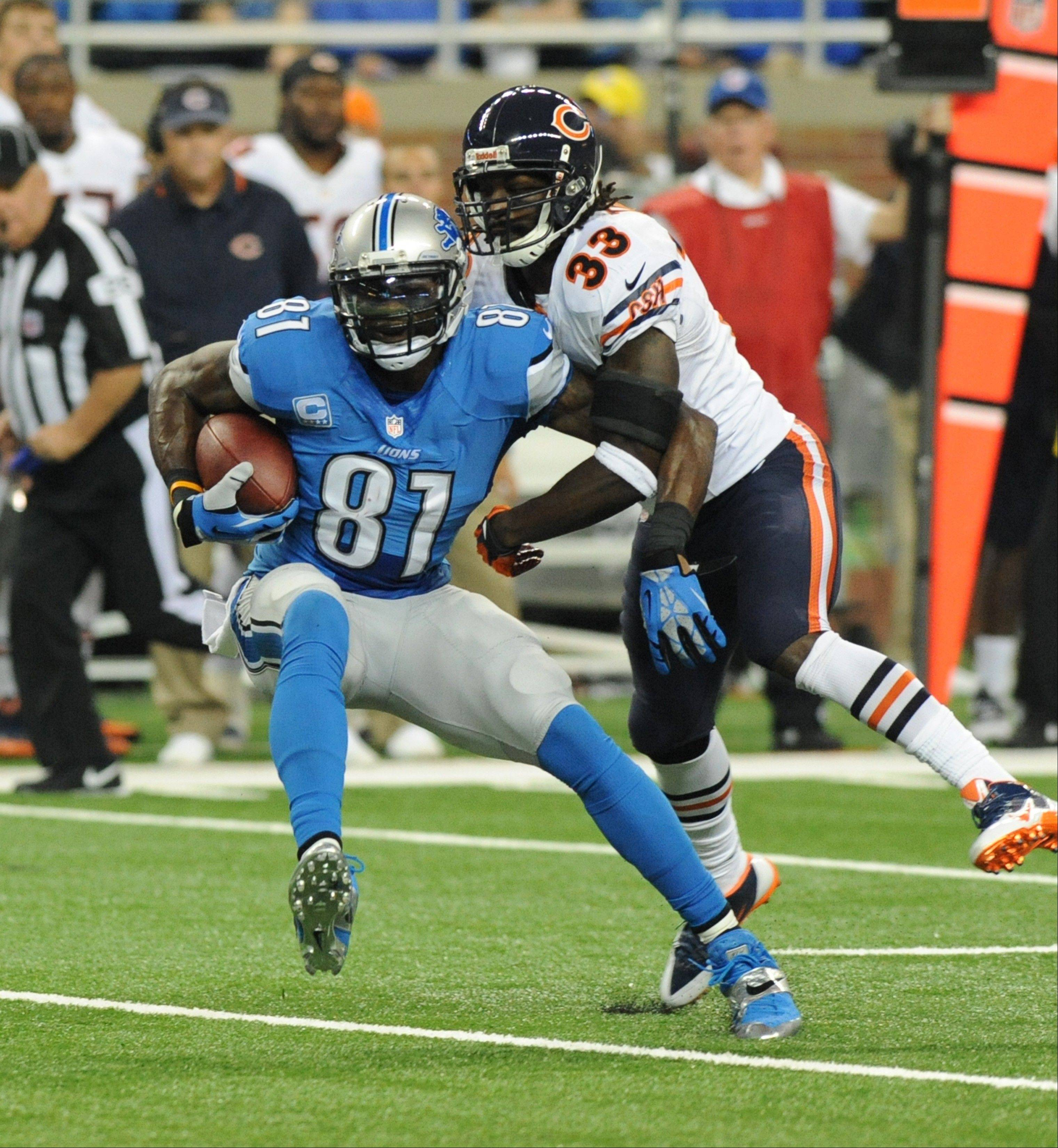 Detroit Lions wide receiver Calvin Johnson (81) makes a reception in front of Chicago Bears cornerback Charles Tillman (33) during the first quarter.