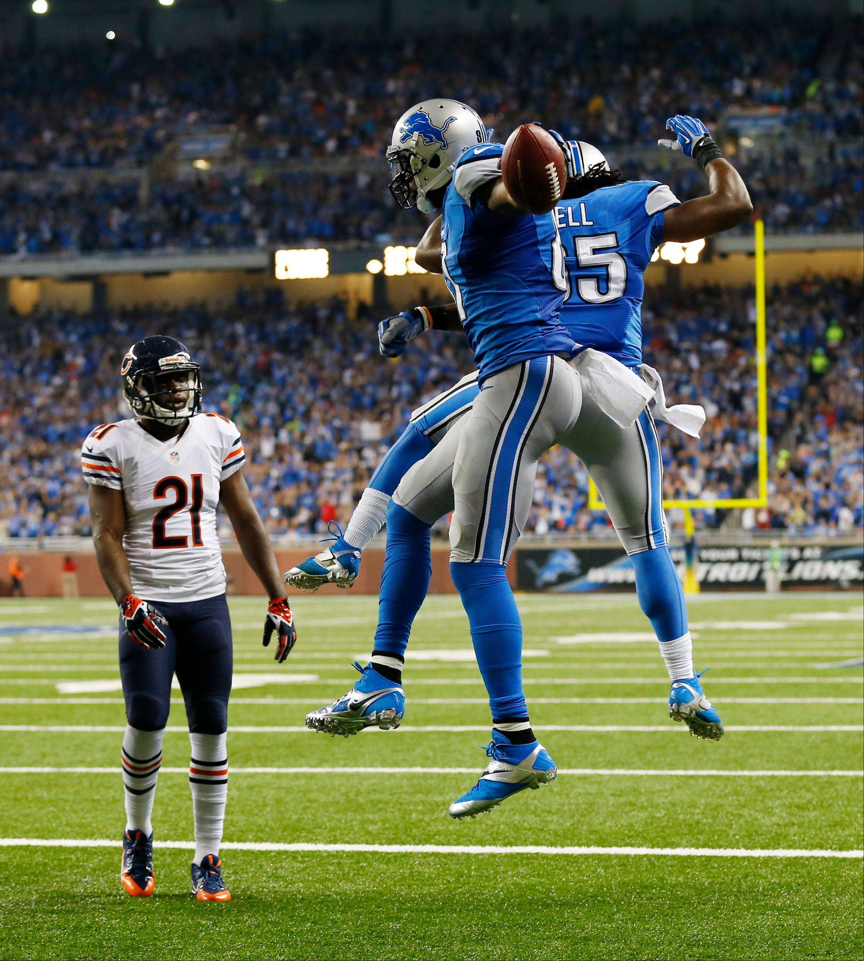 Detroit Lions wide receiver Calvin Johnson (81) and teammate running back Joique Bell (35) celebrate Johnson's touchdown as Chicago Bears strong safety Major Wright (21) look on during the second quarter.
