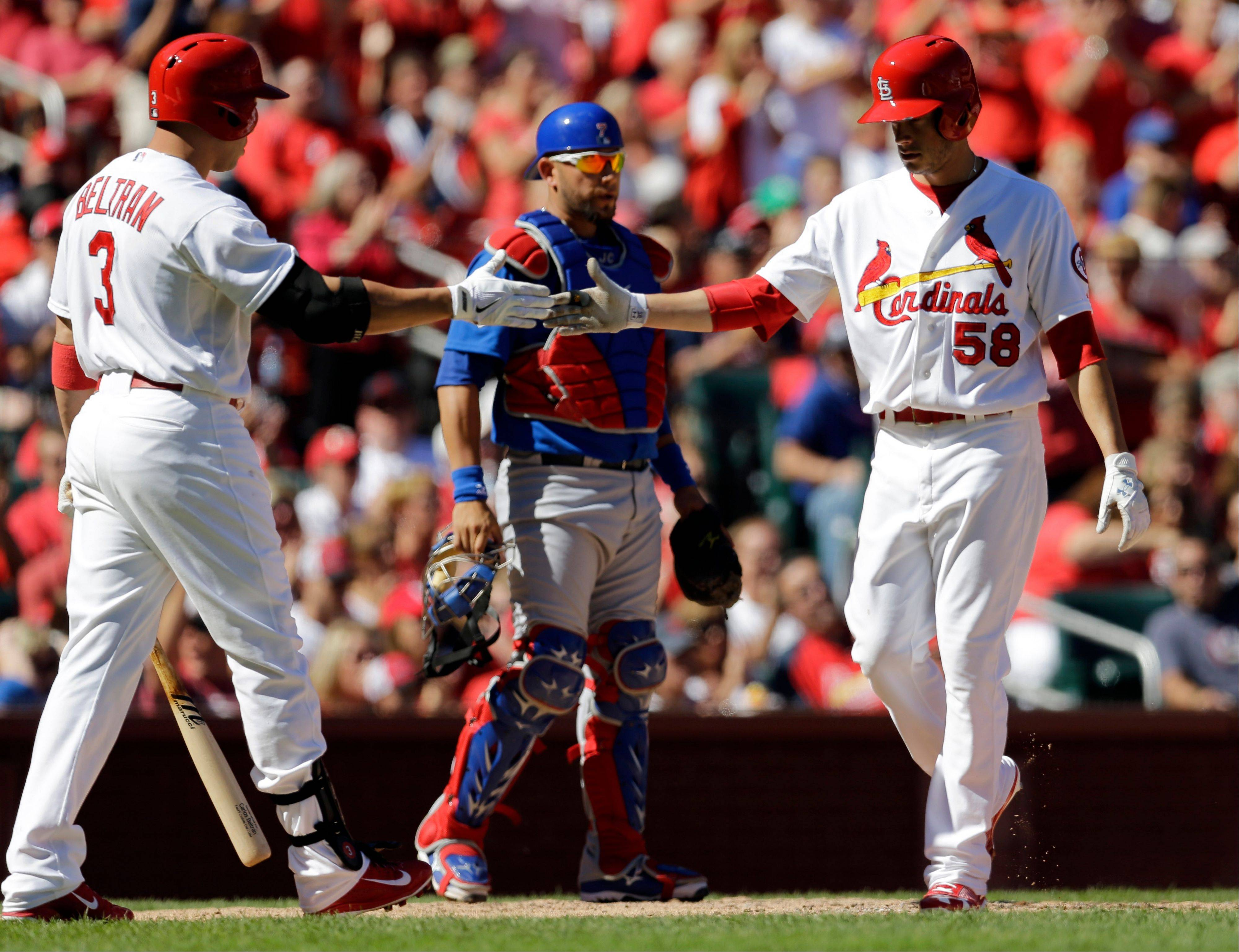 St. Louis Cardinals' Joe Kelly, right, is congratulated by teammate Carlos Beltran after scoring as Chicago Cubs catcher J.C. Boscan, center, looks on during the third inning of a baseball game on Sunday, Sept. 29, 2013, in St. Louis.