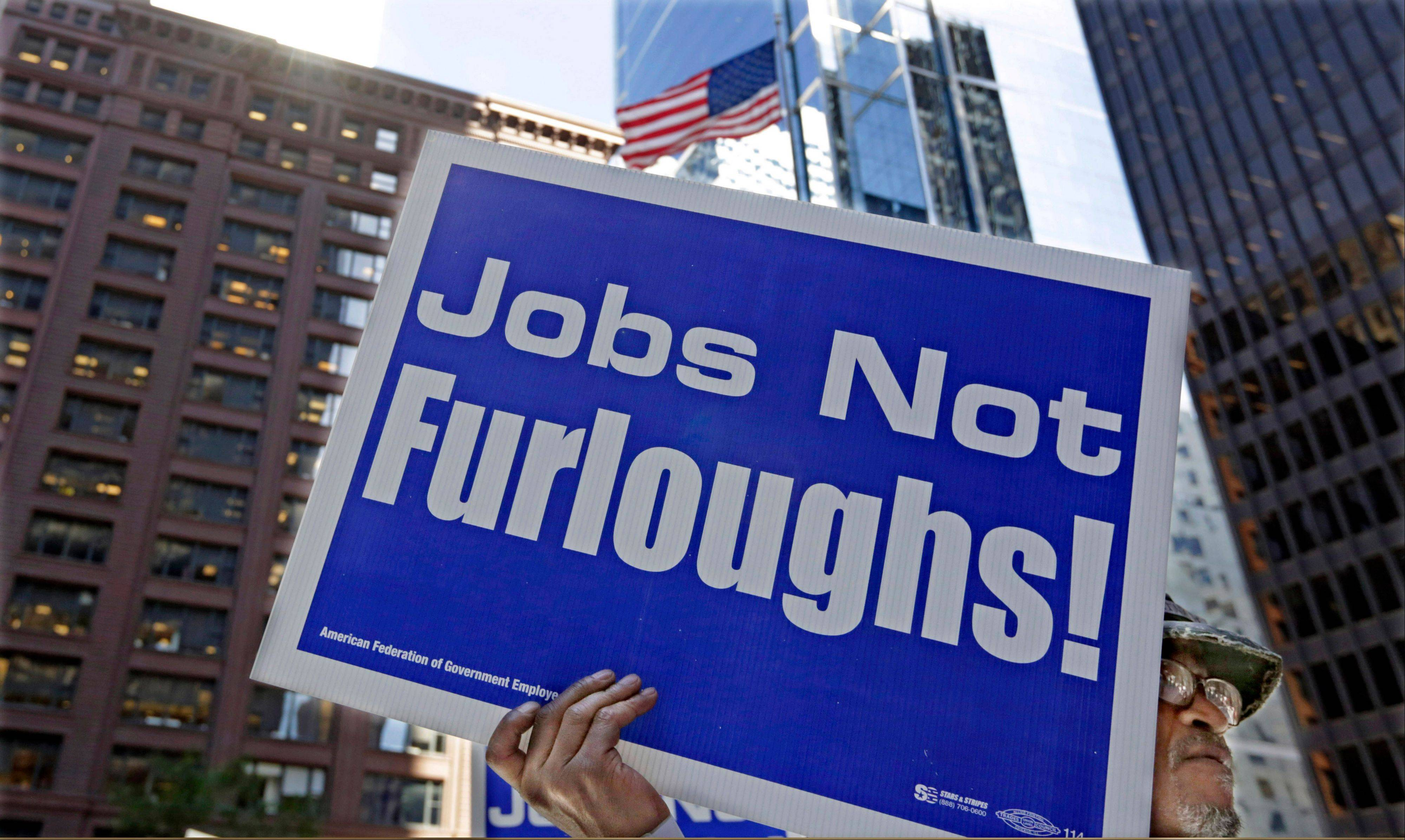 Government workers protest the possibility of a federal shutdown Monday in Chicago. Nearly 100 employees from federal agencies including the Environmental Protection Agency and the Department of Housing and Urban Development rallied in a downtown plaza on Monday. Thousands of workers could be furloughed if the shutdown materializes. The federal government is the nation�s biggest employer.