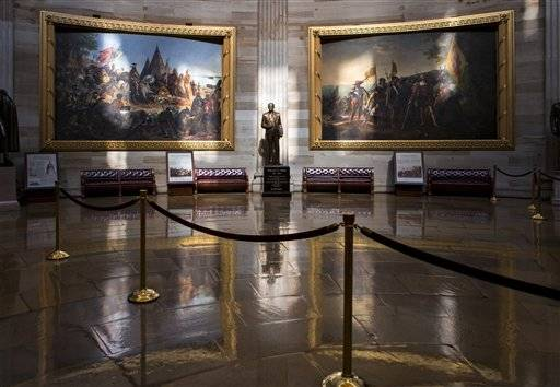 Normally filled with visitors and tourists, the empty Rotunda at the U.S. Capitol is seen in Washington, Tuesday, Oct. 1, 2013, after officials suspended all organized tours of the Capitol and the Capitol Visitors Center as part of the government shutdown. A statue of President Gerald R. Ford at center is illuminated amid large paintings illustrating the history of the United States. (AP Photo/J. Scott Applewhite)