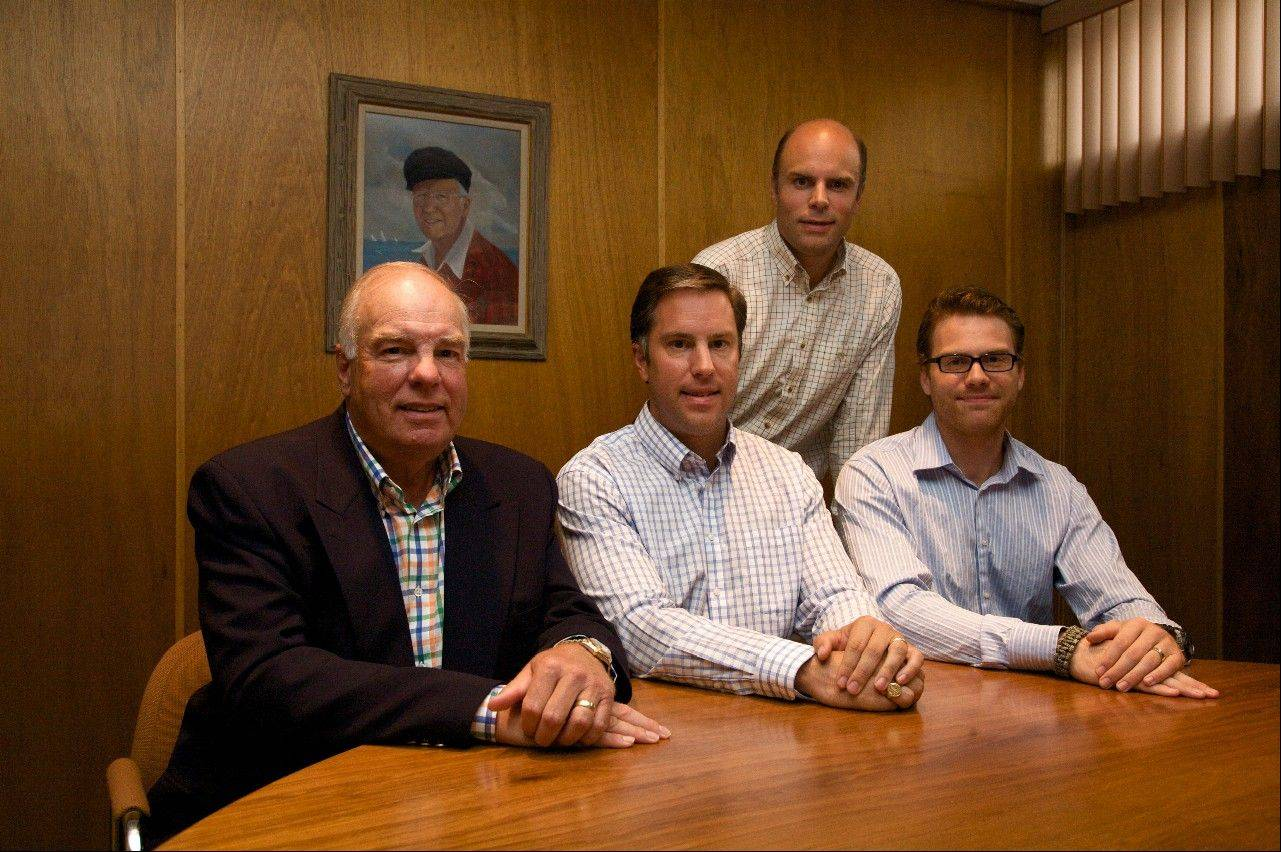 Ken Larson, picture on the on wall, founded Precision Instruments in Des Plaines. His family now runs the business. John Larson Sr. (sitting left) is the second generation while John Larson Jr. is starting the third generation. Matthew Larson and Andrew Larson, standing, assist in the operation as well.