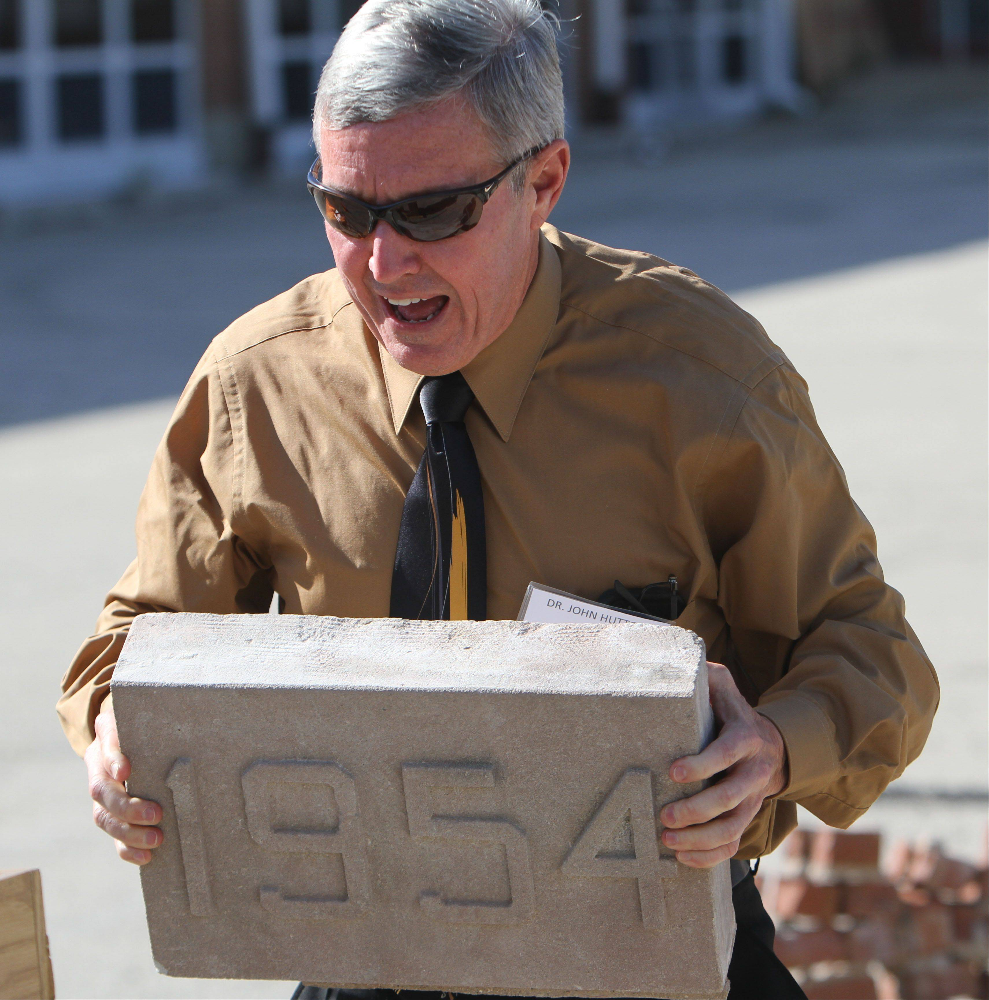 Gurnee Elementary District 56 Superintendent John Hutton holds the cornerstone from the Gurnee Grade School during an event Monday marking the beginning of demolition.