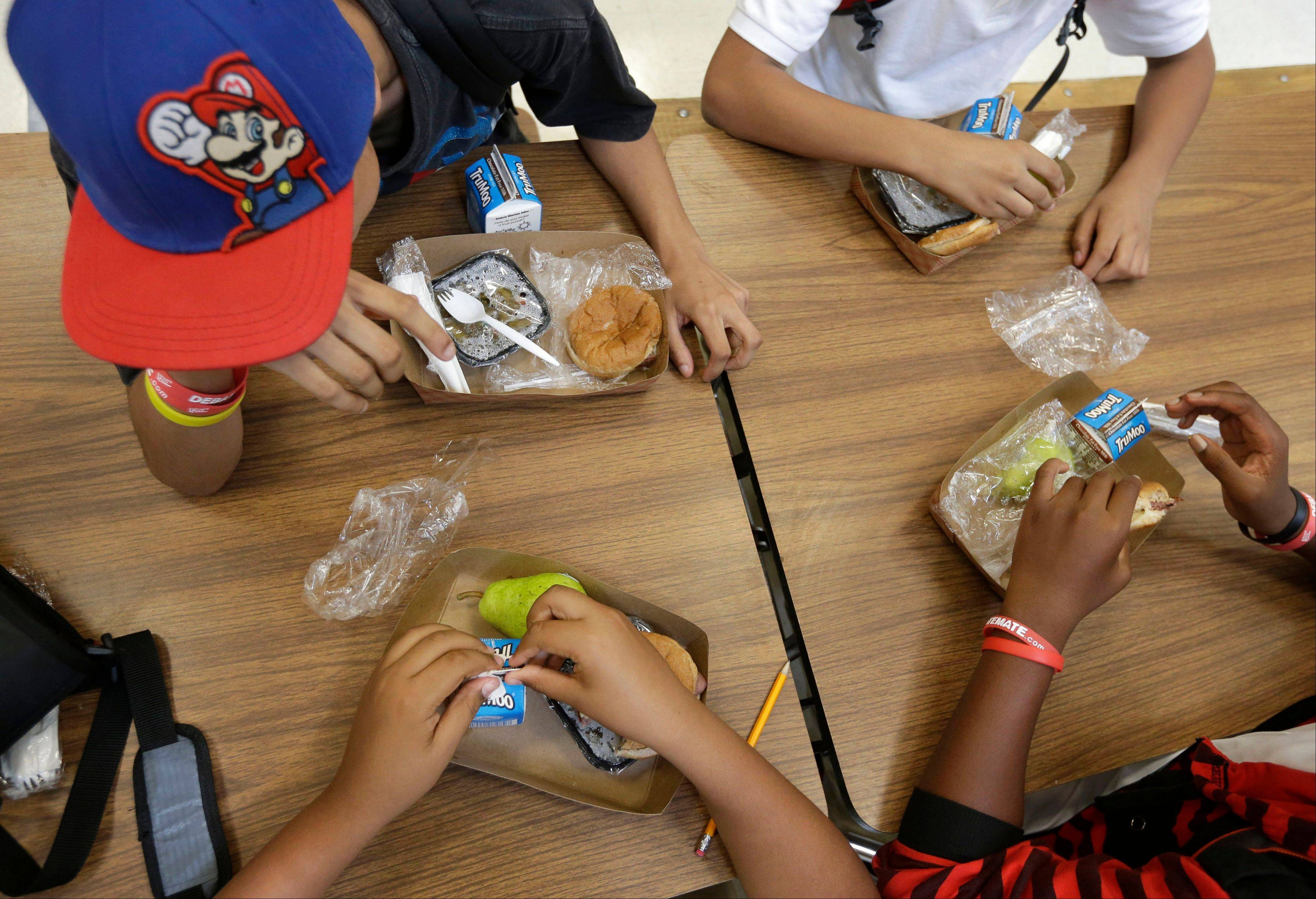 Students at the Maurice J. Tobin K-8 School in Boston's Roxbury neighborhood eat free lunches consisting of a sandwich with meat, a vegetable dish, a piece of fruit, and milk. The Agriculture Department says that around half a percent of schools _ or 524 schools out of around 100,000 _ have dropped out of the federally-subsidized national school lunch program since the government put new standards for healthier foods in place last year.