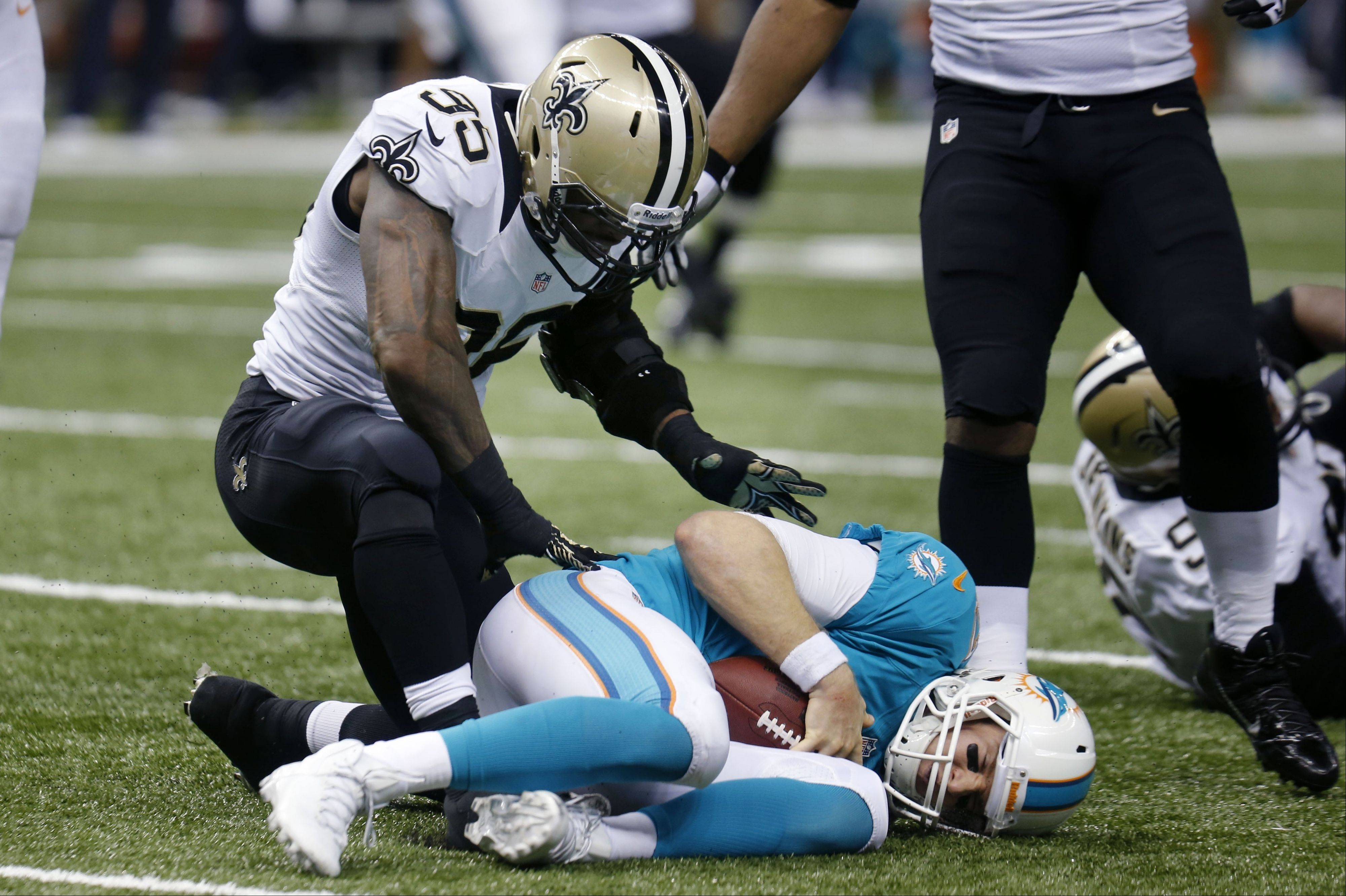 Miami Dolphins quarterback Ryan Tannehill lies on the turf after being sacked by Saints linebacker Martez Wilson (95) in the second half of Monday�s game in New Orleans.