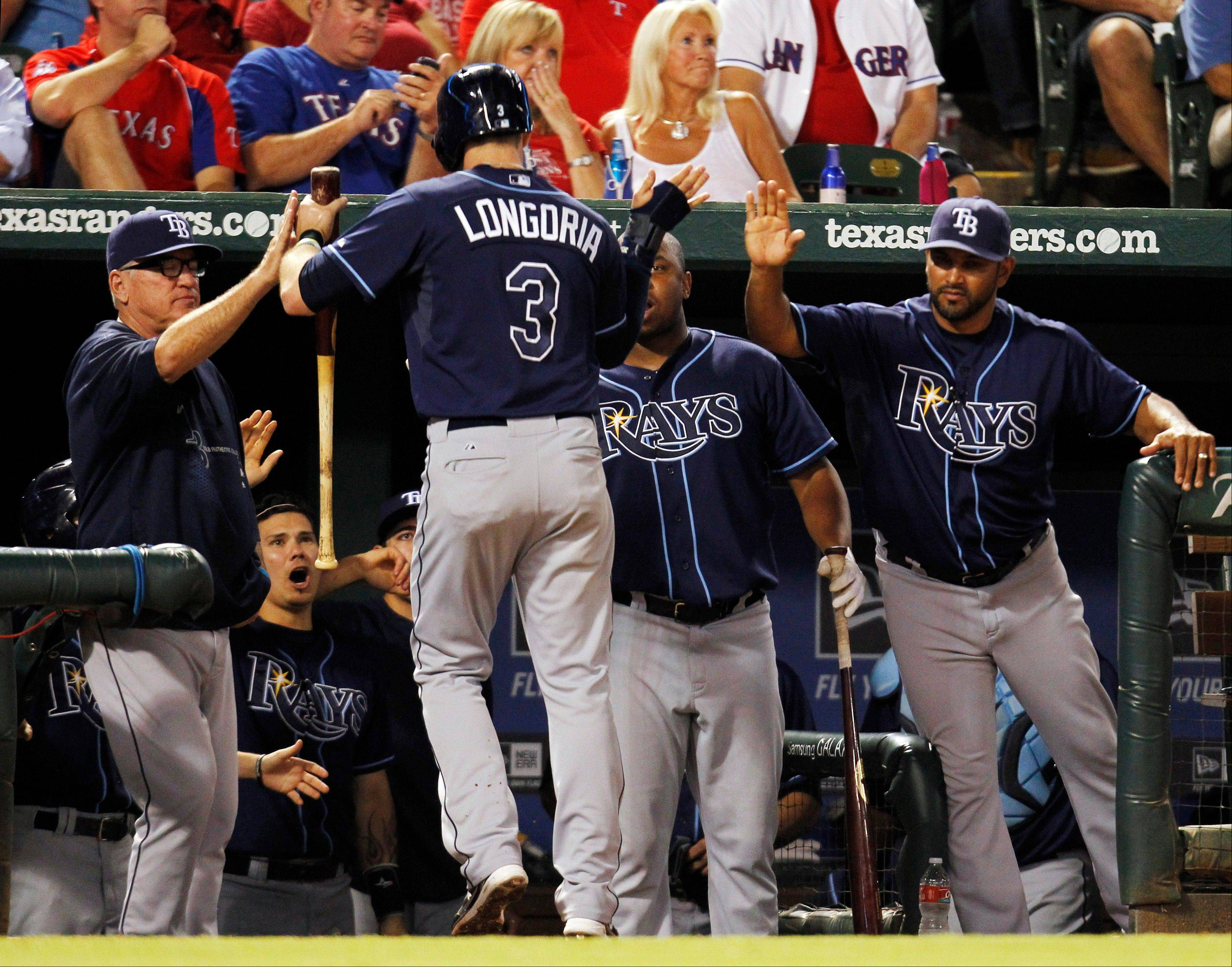 Tampa Bay�s Evan Longoria celebrates after scoring on a double by David DeJesus during the sixth inning Monday against the Texas Rangers in Arlington, Texas.