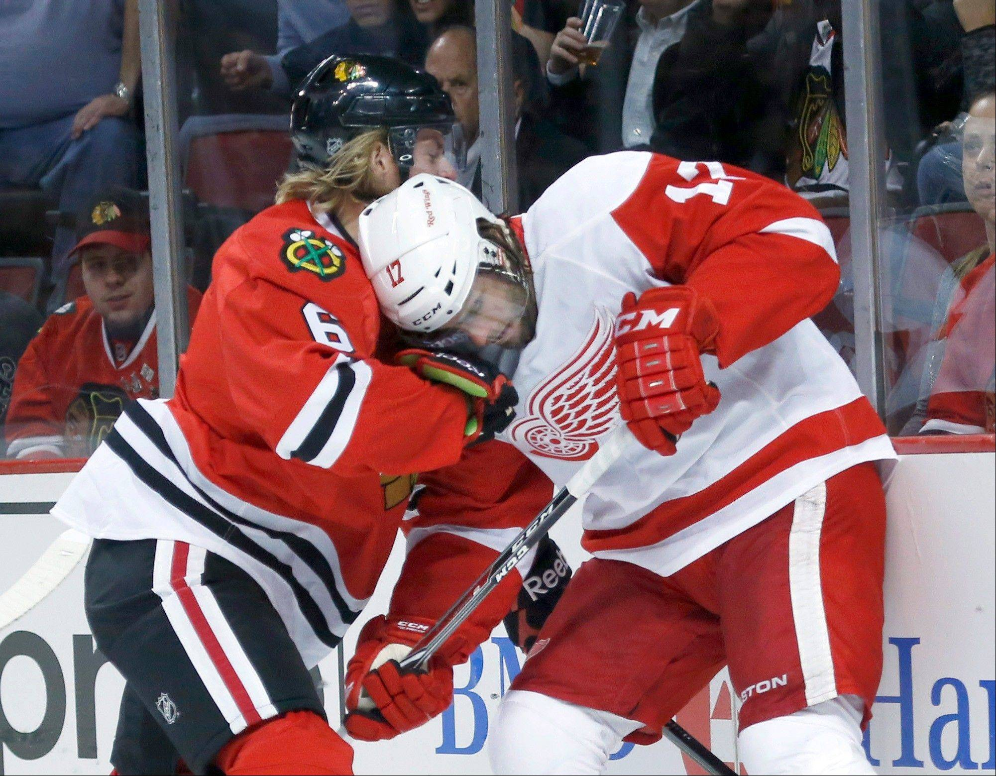 Blackhawks defenseman Mike Kostka, here battling Detroit right wing Patrick Eaves for the puck, earned the eighth spot on the Hawks defense after joining the team as a free agent.