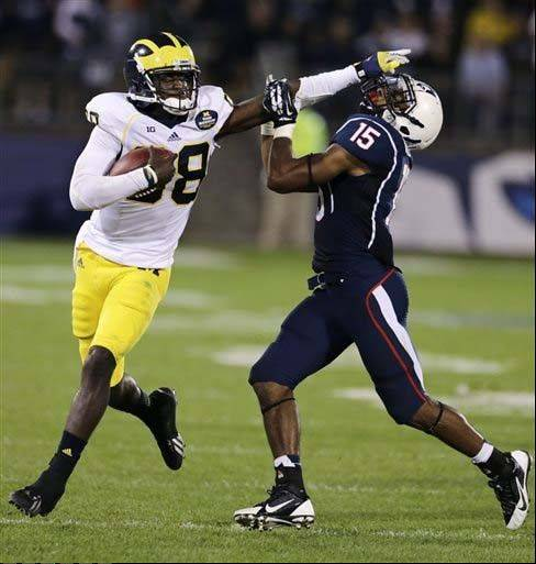 Michigan quarterback Devin Gardner straight-arms Connecticut safety Ty-Meer Brown during the Sept. 21 game in East Hartford, Conn. To win the Big Ten title, Michigan has to figure out a way to do a better job of moving the ball on the ground to take pressure off Gardner.