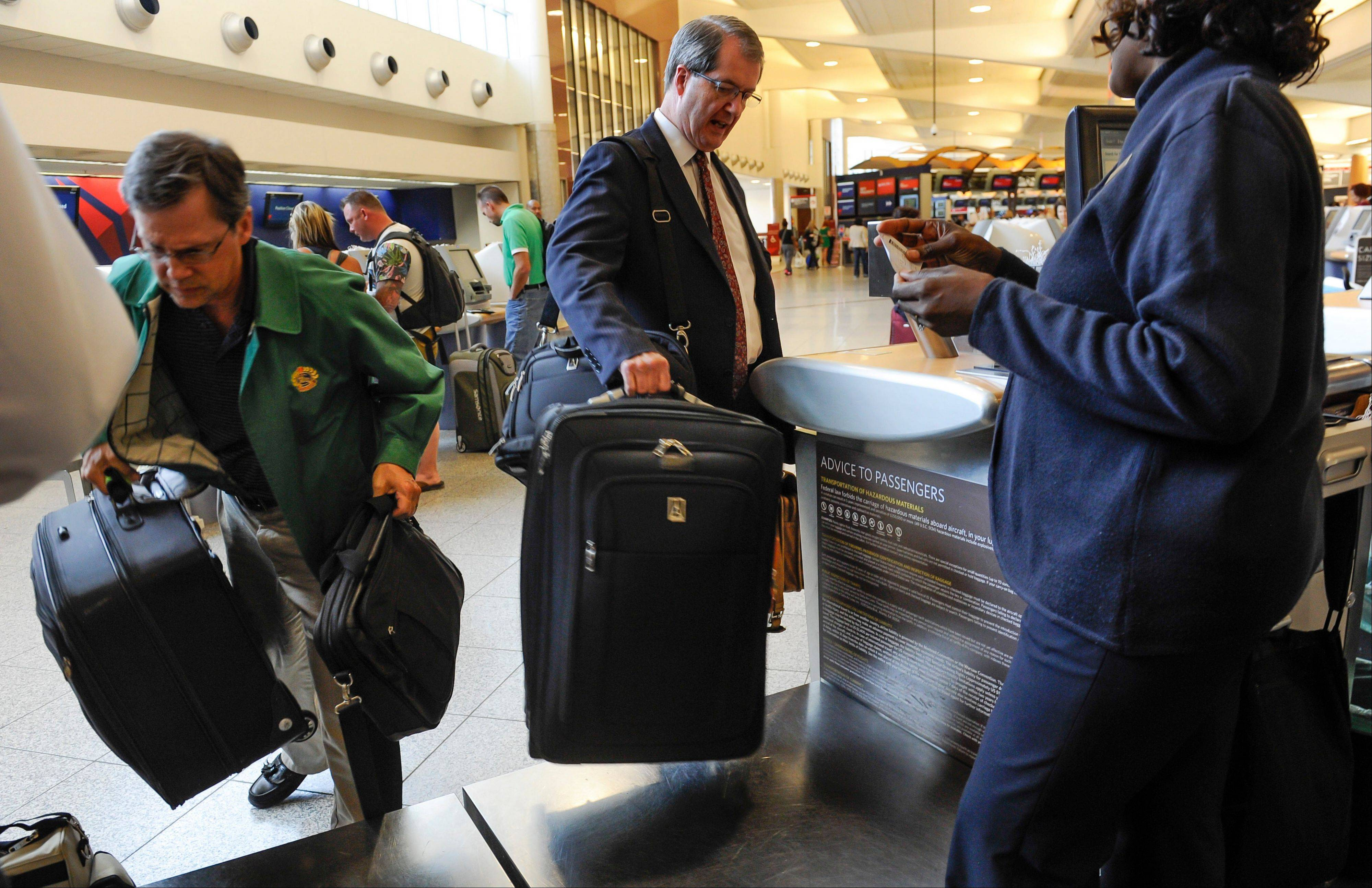 Passengers check in their luggage at the Delta counter at Hartsfield-Jackson Atlanta International Airport in Atlanta. Delta customers now have the option to purchase an upgrade that includes a free checked bag, among other perks.