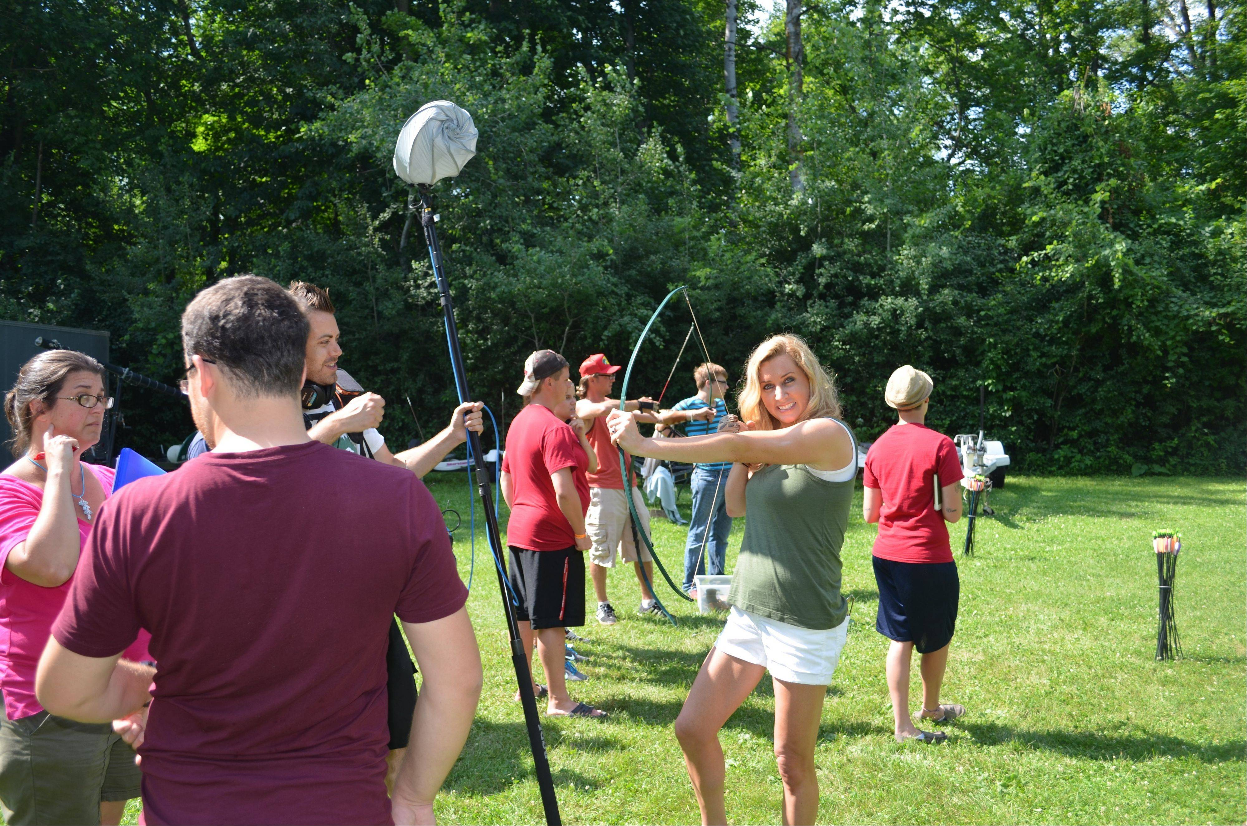 "Colleen Kelly, of Mount Prospect, poses with a bow and arrow at a family camp in Wisconsin while filming her national PBS series, ""Family Travel with Colleen Kelly."""