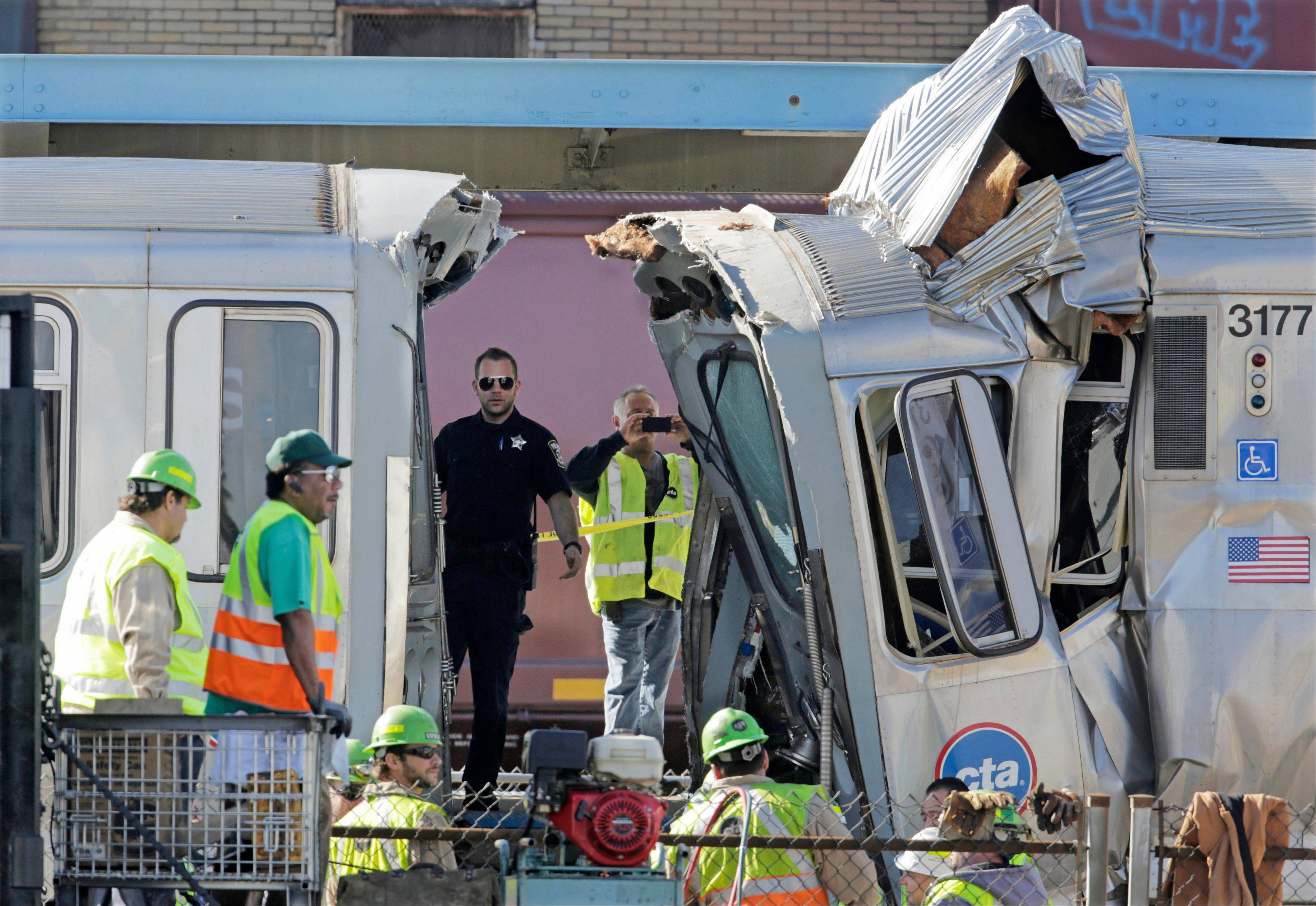 Authorities inspect the wreckage of two Chicago Transit Authority trains that crashed Monday