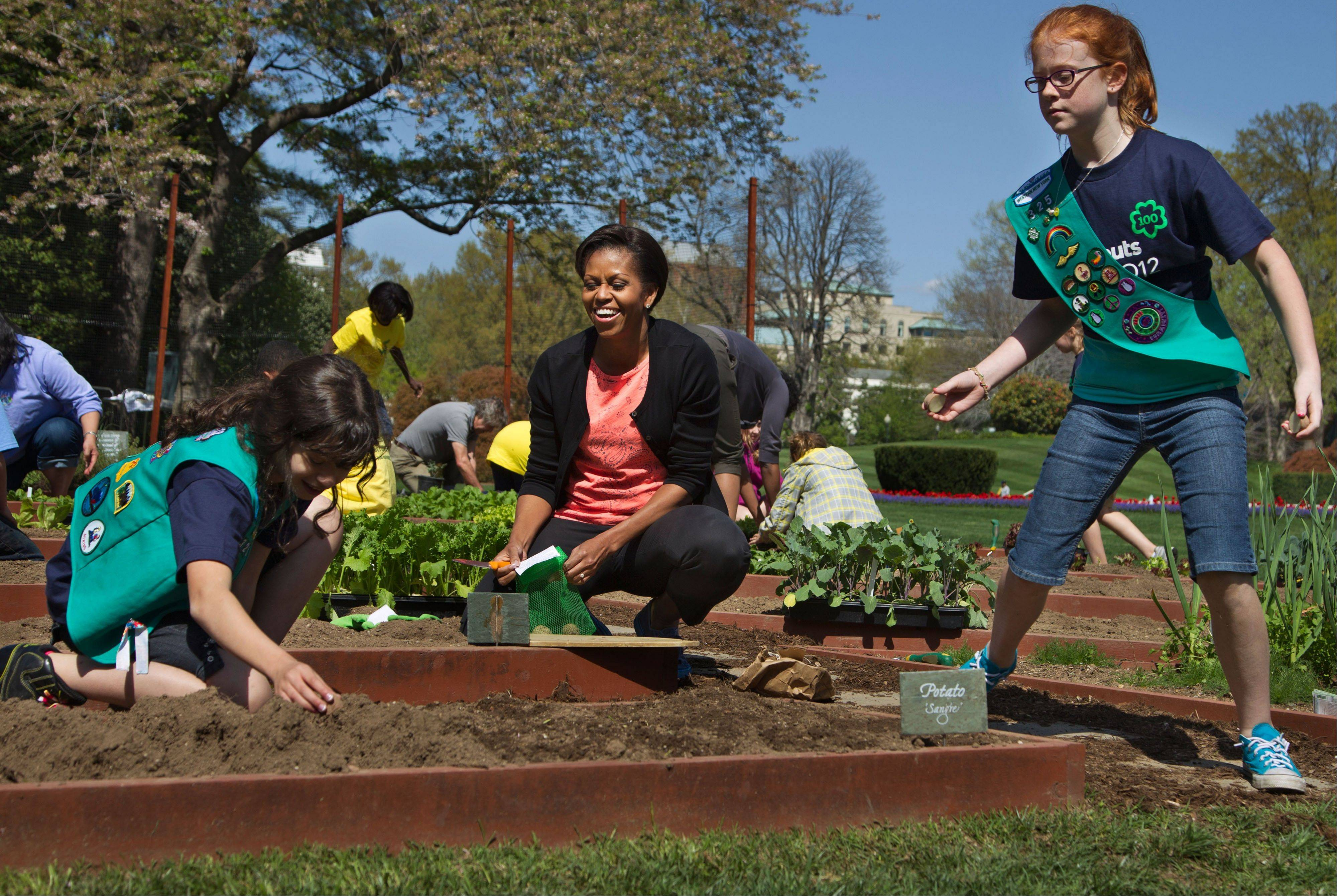 First lady Michelle Obama, center, laughs as she and Girl Scouts Gia Muto, left, and Emily Burnham, from Fairport, N.Y. plant potatoes during a spring planting of the White House kitchen garden at the White House in Washington. With an assist from Michelle Obama, the Girl Scouts of the USA is launching an unorthodox recruitment campaign aimed at reversing a long-running decline in participation by girls and adult volunteers.