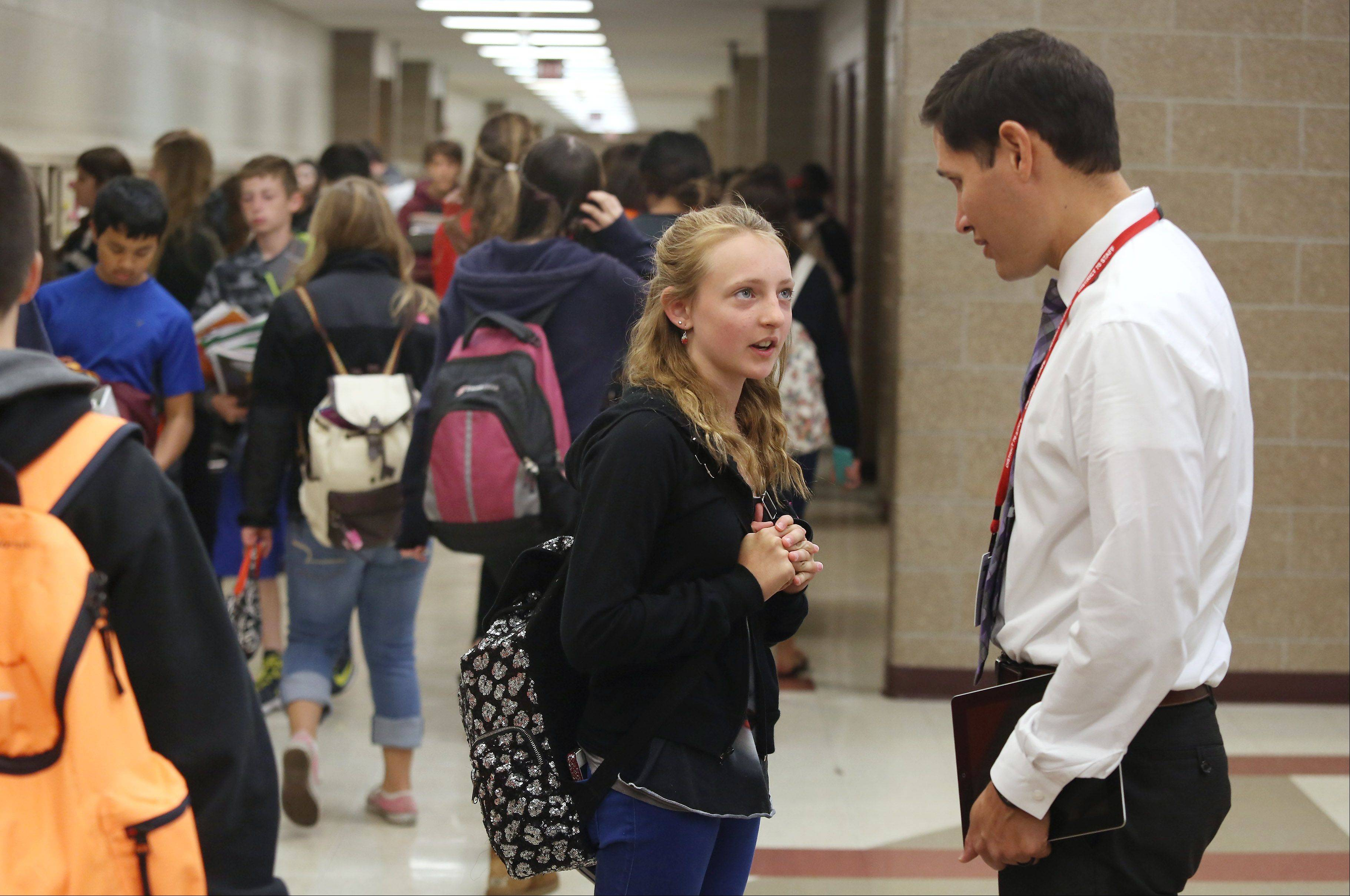 Highland Middle School Assistant Principal Lorenzo Cervantes talks to seventh-grader Madison Hartwig as students switch classes. Cervantes has been involved with the new online bullying forms at the Libertyville school.