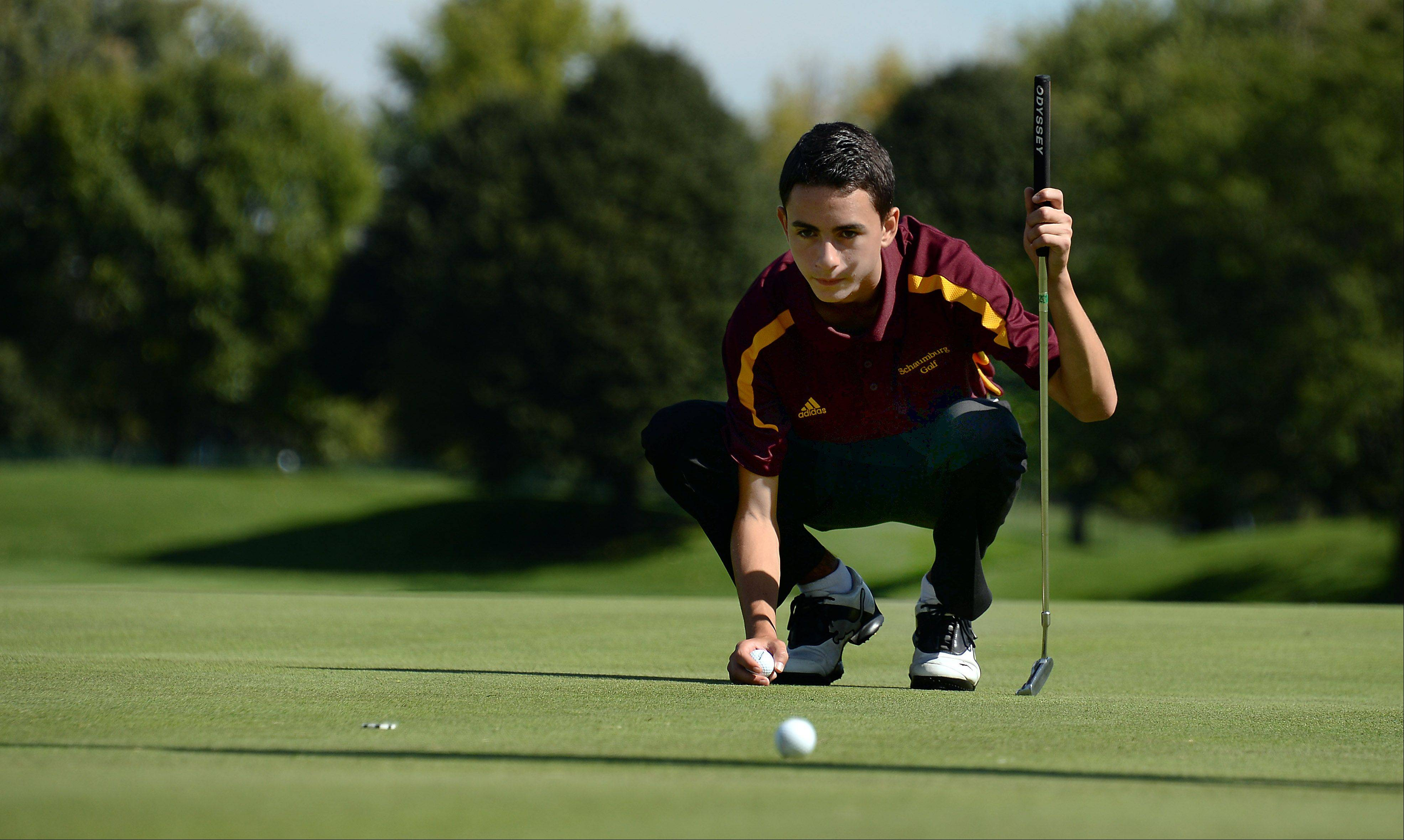 Schaumburg's Brandon Tudor lines up his putt on No. 19 during the Mid-Suburban League championship at Schaumburg Golf Club on Monday.