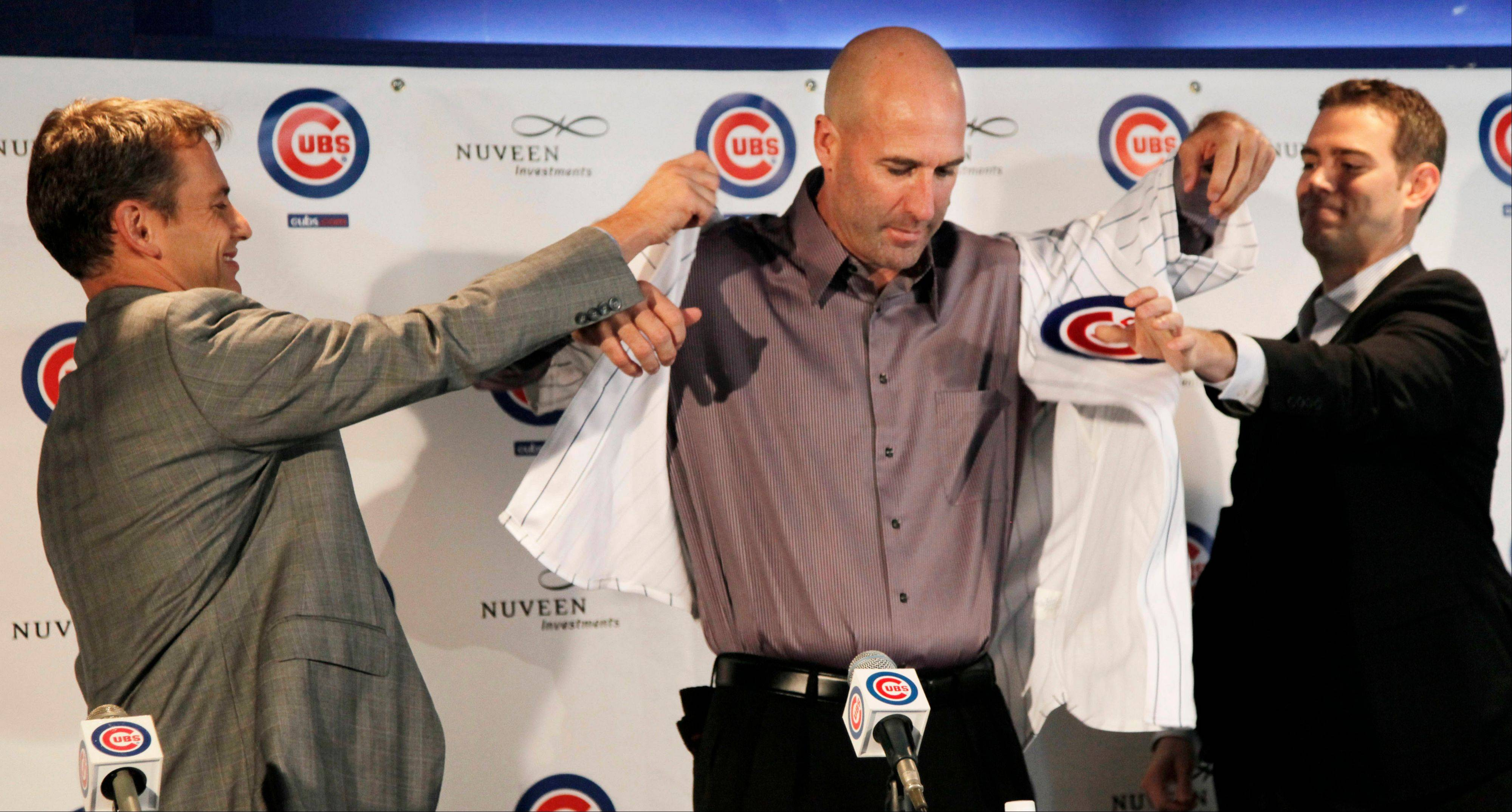 Chicago Cubs general manager Jed Hoyer, left, and president Theo Epstein, right, help new manager Dale Sveum put on Cubs jersey as he is introduced during a baseball news conference, Friday, Nov. 18, 2011, in Chicago.