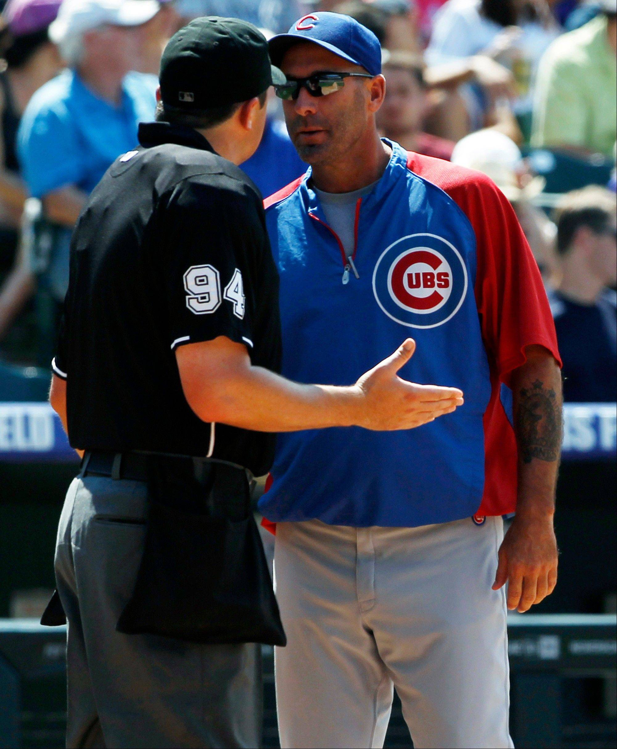 Chicago Cubs manager Dale Sveum, right, argues call with home plate umpire Lance Barrett, left, while facing the Colorado Rockies in the fourth inning of a baseball game in Denver, Sunday, July 21, 2013.