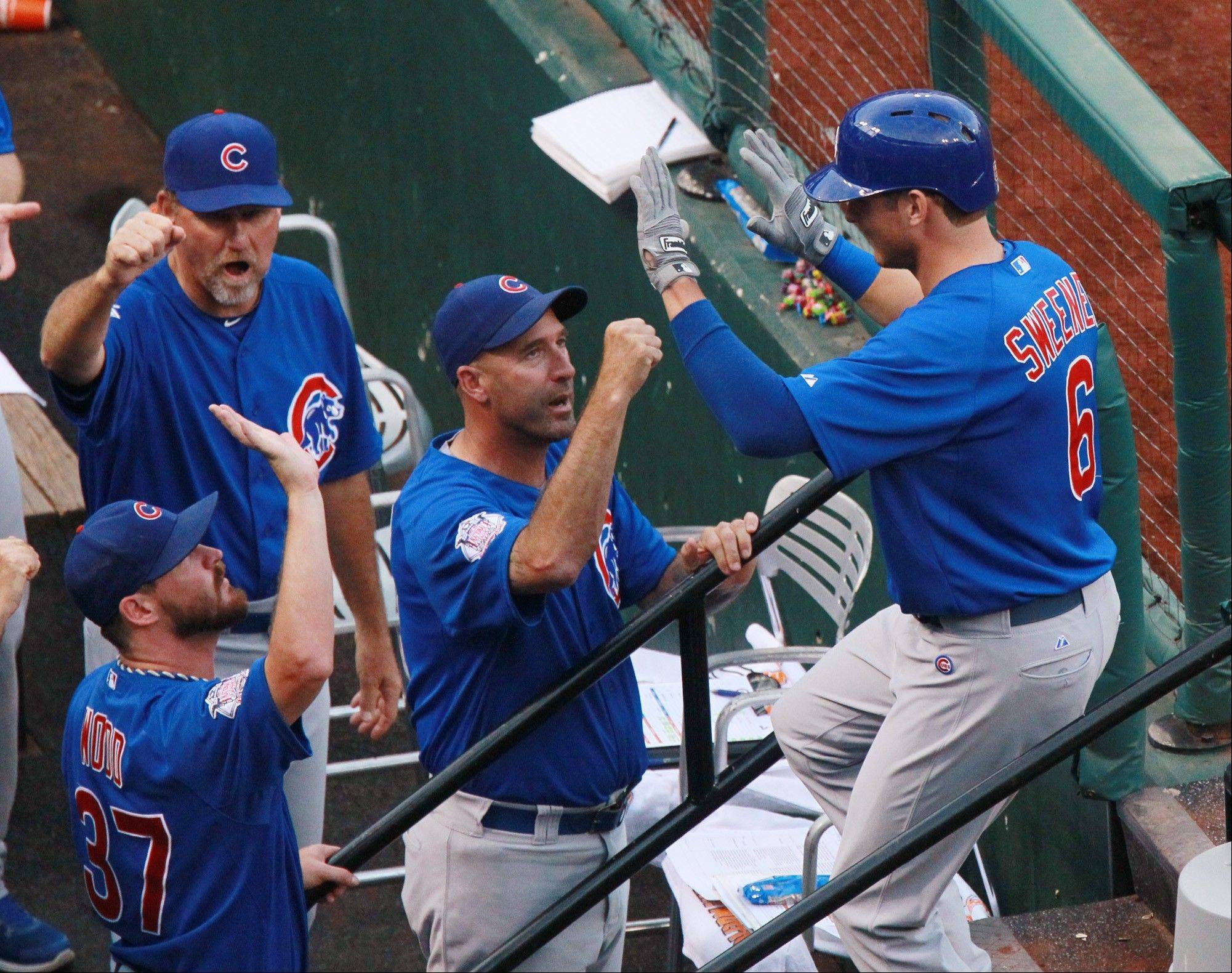 Chicago Cubs' Ryan Sweeney, right, is congratulated by manager Dale Sveum, center, as he returns to the dugout after hitting a two-run home run in the first inning of a baseball game against the St. Louis Cardinals on Tuesday, June 18, 2013, in St. Louis.
