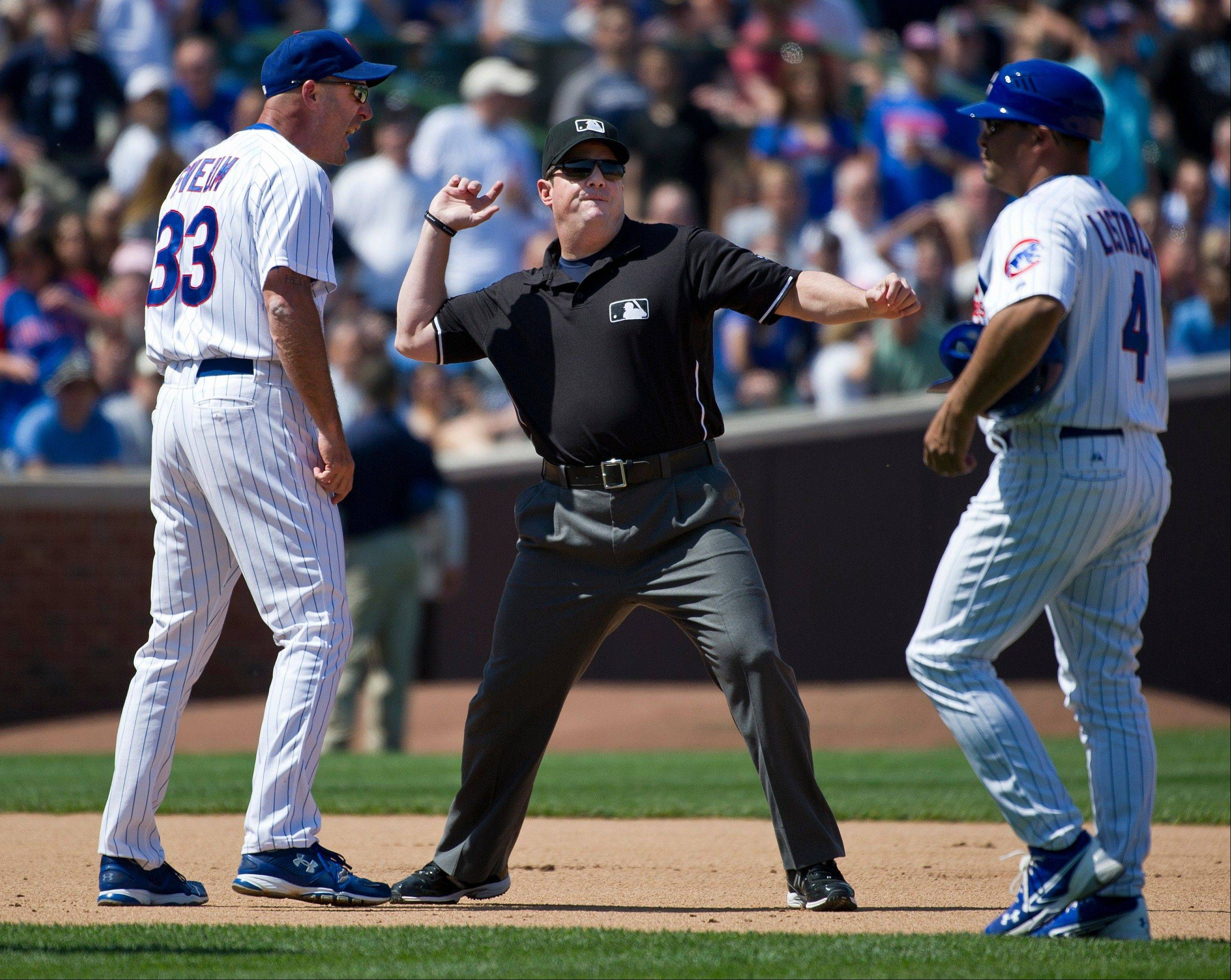Second base umpire Eric Cooper, center, ejects Chicago Cubs manager Dale Sveum, left, after Sveum came out to argue a call during the fifth inning of an imterleague baseball game against the Chicago White Sox, Friday, May 18, 2012 in Chicago. Cubs third base coach Pat Listach watches the argument.
