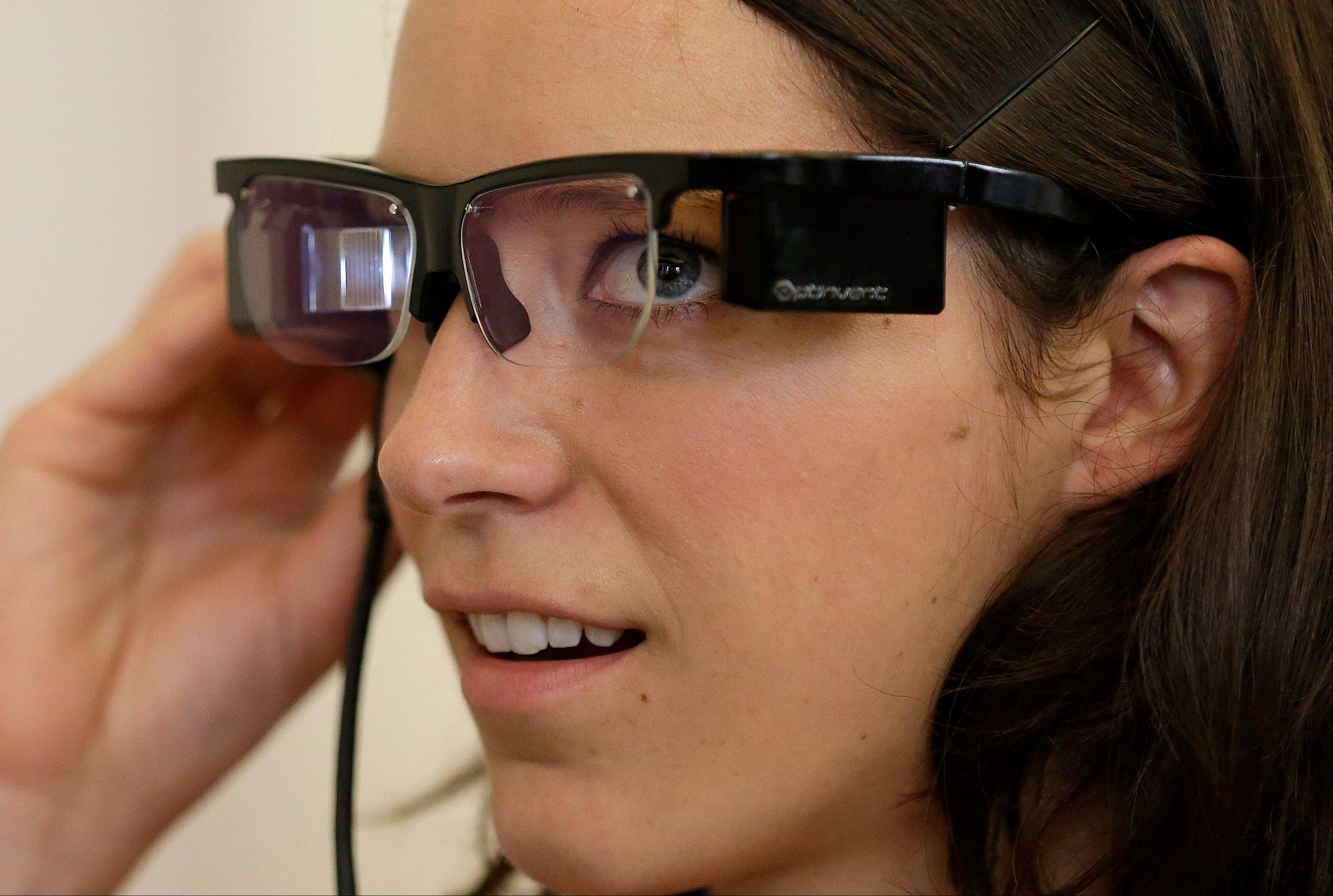 Claire Collins is given a demonstration of Optinvent ORA-S augmented reality glasses at the GLAZED Conference, a conference for the business of wearable technology, in San Francisco, Monday.