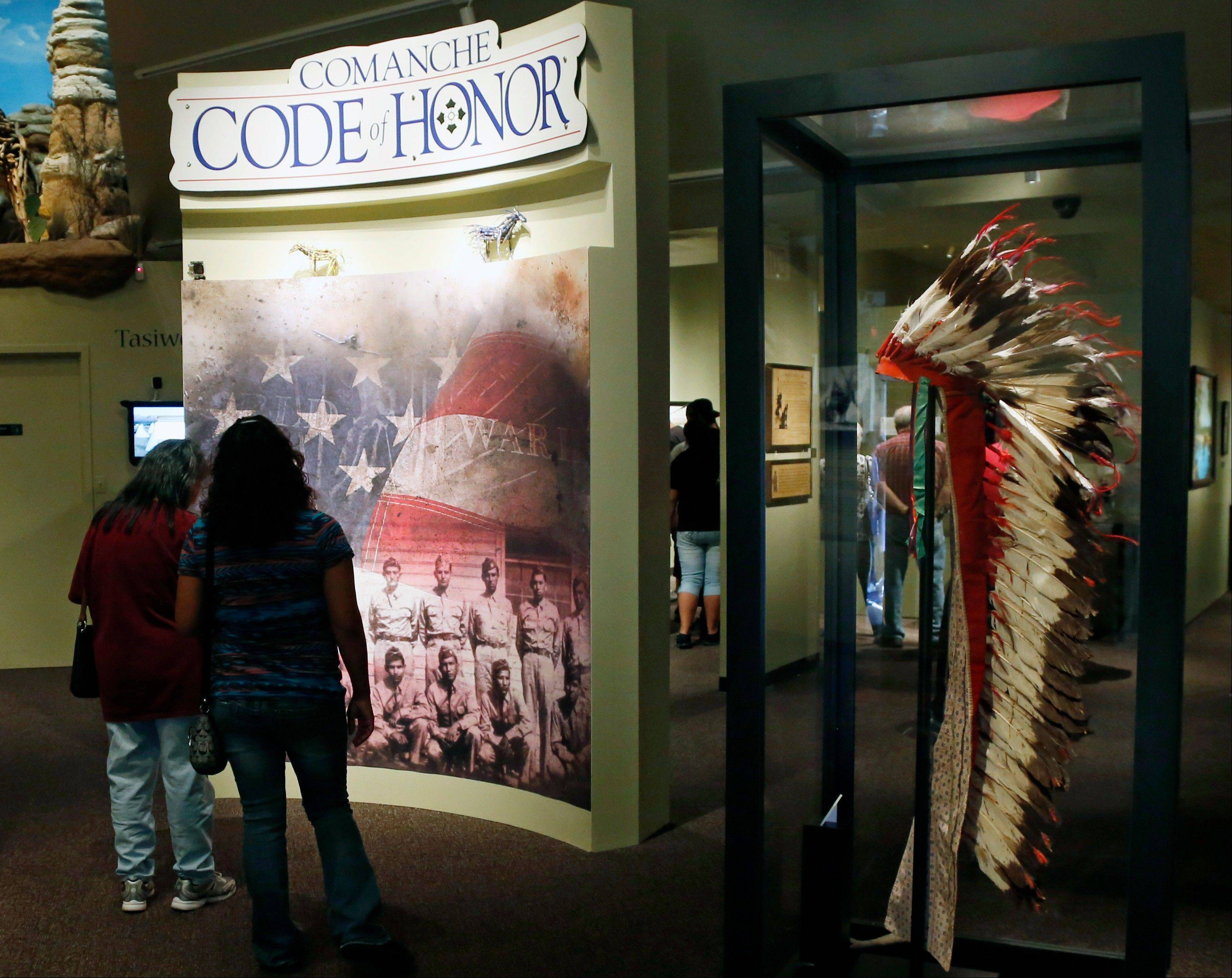 Visitors walk through an exhibit about the Comanche Code Talkers at the Comanche National Museum and Cultural Center in Lawton, Okla.