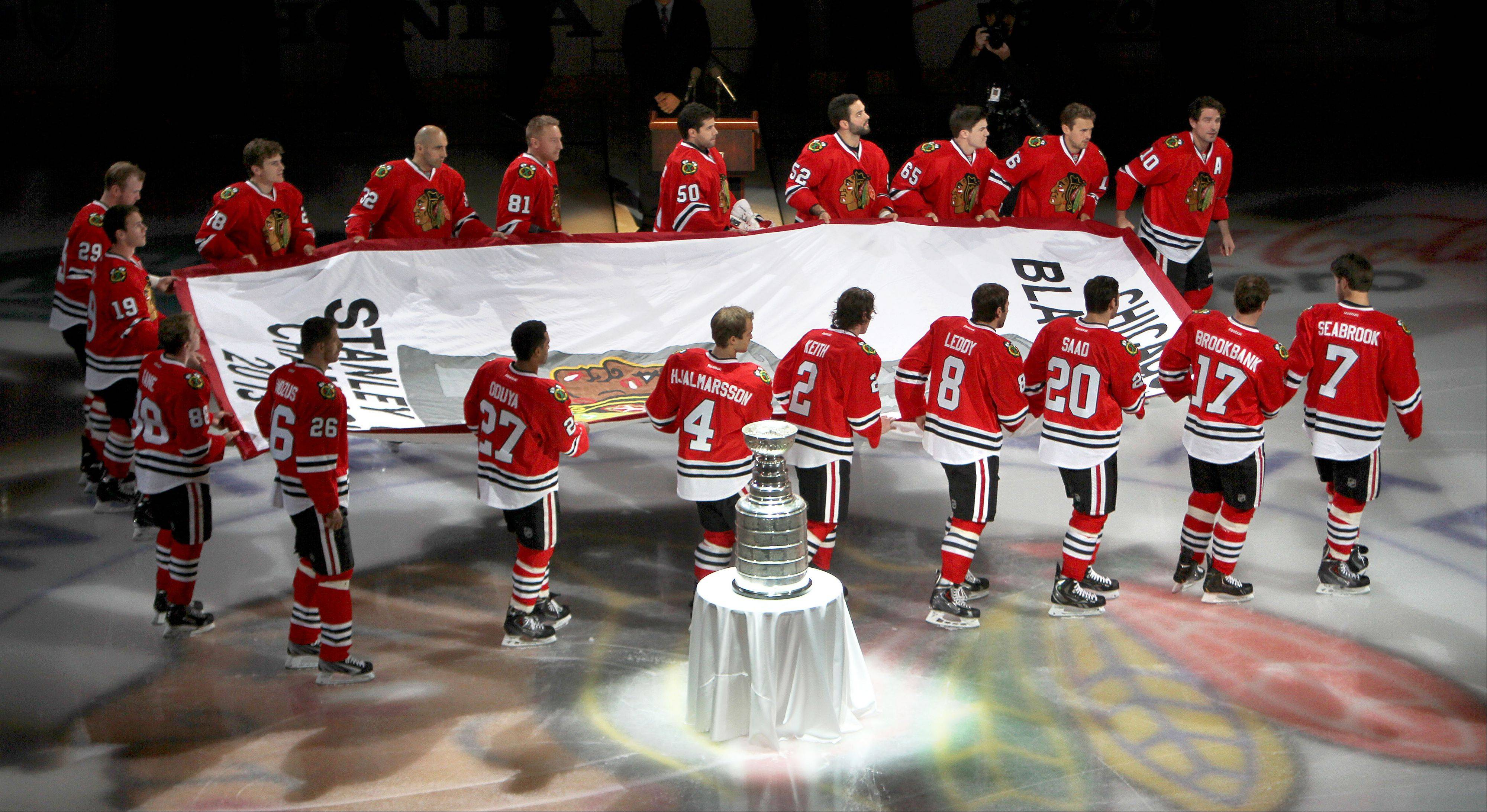 Blackhawks teammates skate with their 2103 Stanley Cup banner.