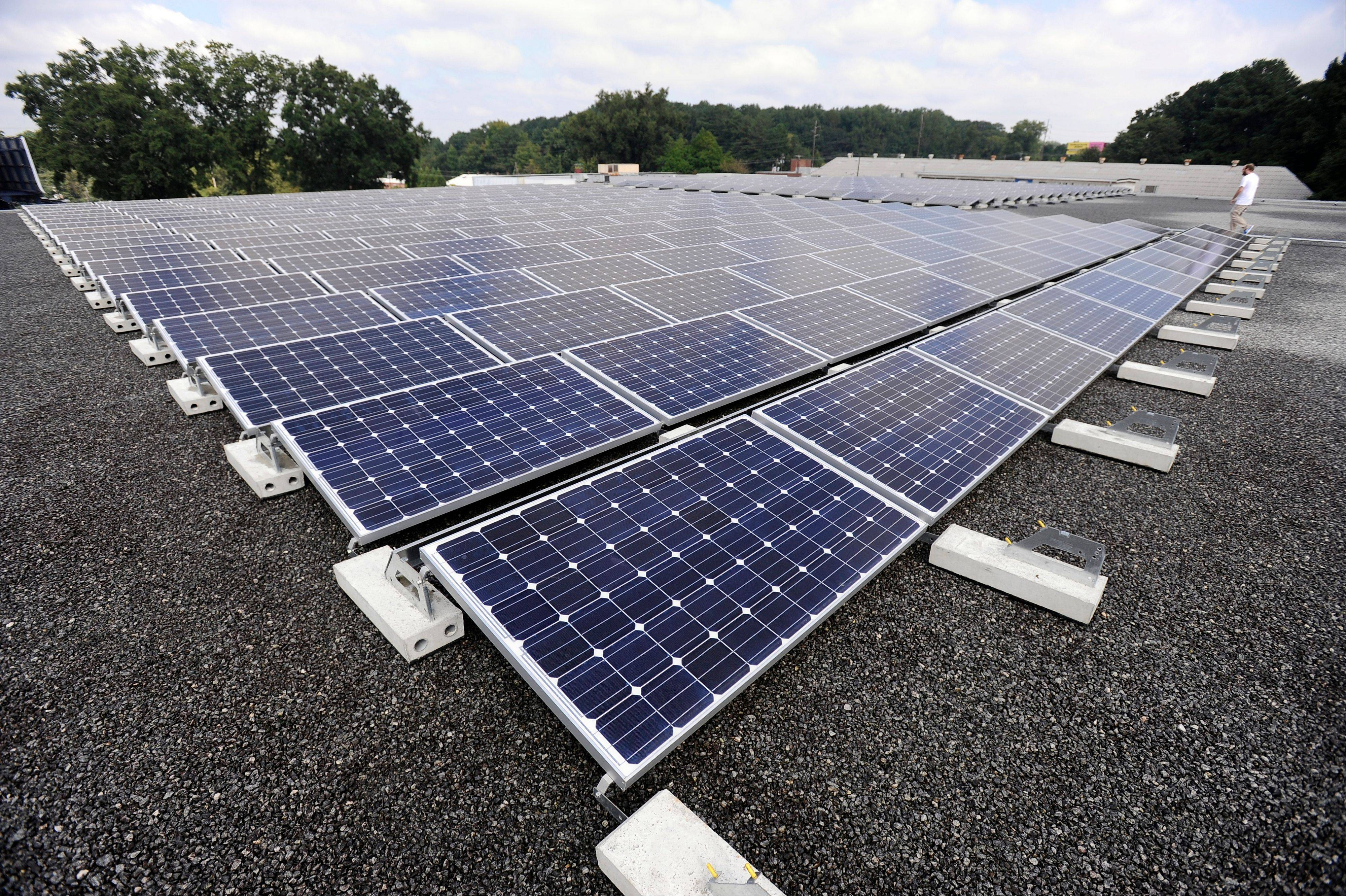 An array of solar cells are seen on the roof of a building in Decatur, Ga. The building's owner returns excess electricity to the Georgia Power Company electrical grid in exchange for a reduced monthly rate.