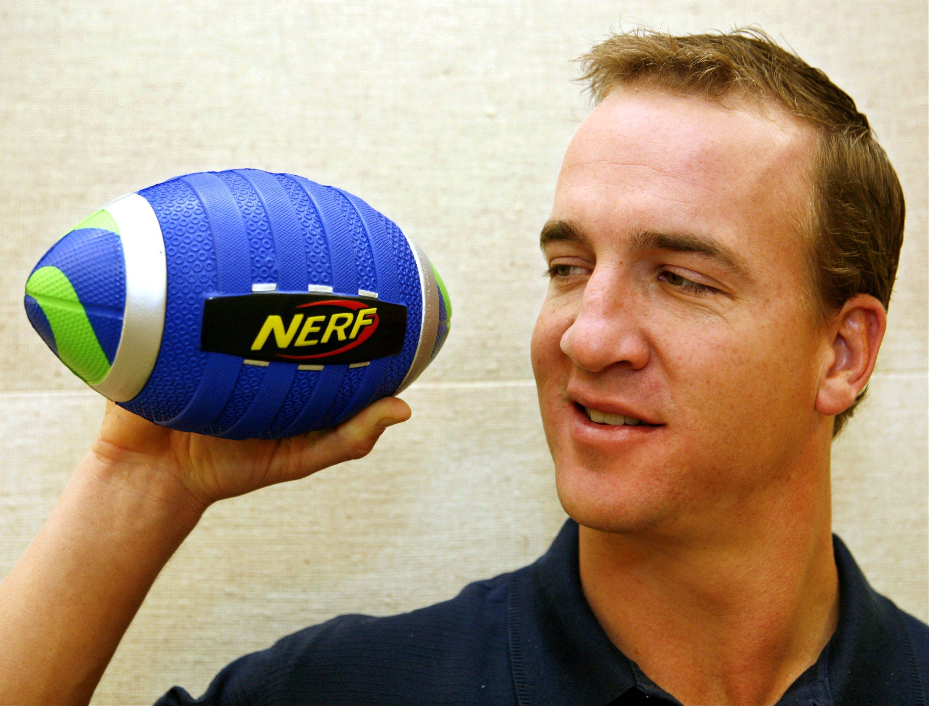 Did star NFL quarterback Peyton Manning toss a Nerf football as he grew up? He's seen here with a model named after him. Nerf toys may are among the 12 finalists for the National Toy Hall of Fame.