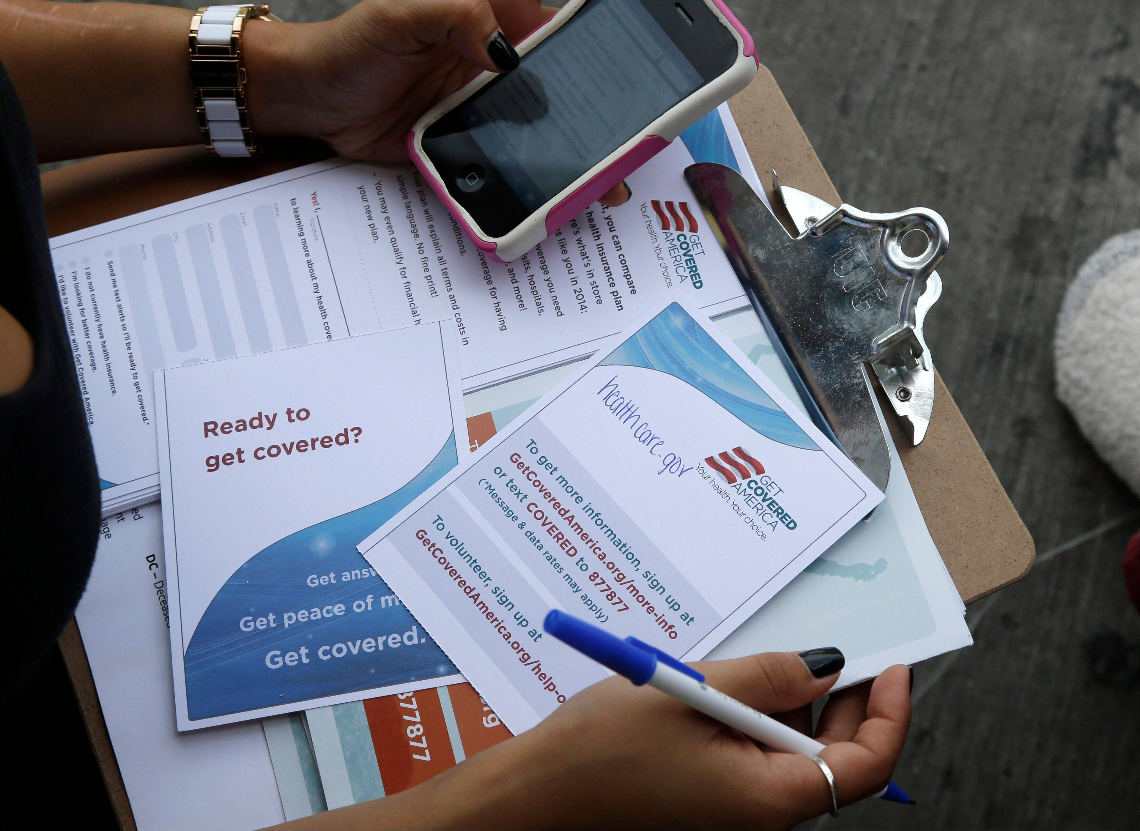 Maygan Rollins, 22, a field organizer with Enroll America, holds a clipboard with pamphlets while canvassing at a bus stop in Miami. Millions of Americans will be able to shop for the first time today on the insurance marketplaces that are at the heart of President Barack Obama's health care reforms.