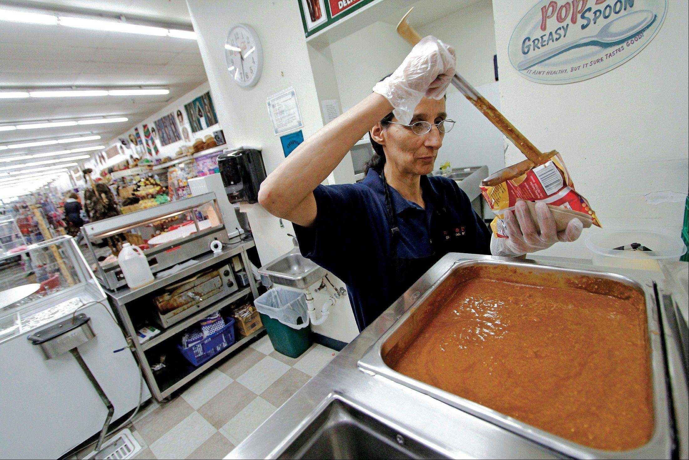 "Loraine Chavez prepares a Frito Pie for a costumer at the Five & Dime in Santa Fe, N.M. The tourist attraction and a mainstay in the city's historic plaza was recently insulted by food critic Anthony Bourdain on an episode of CNN's ""Parts Unknown""."