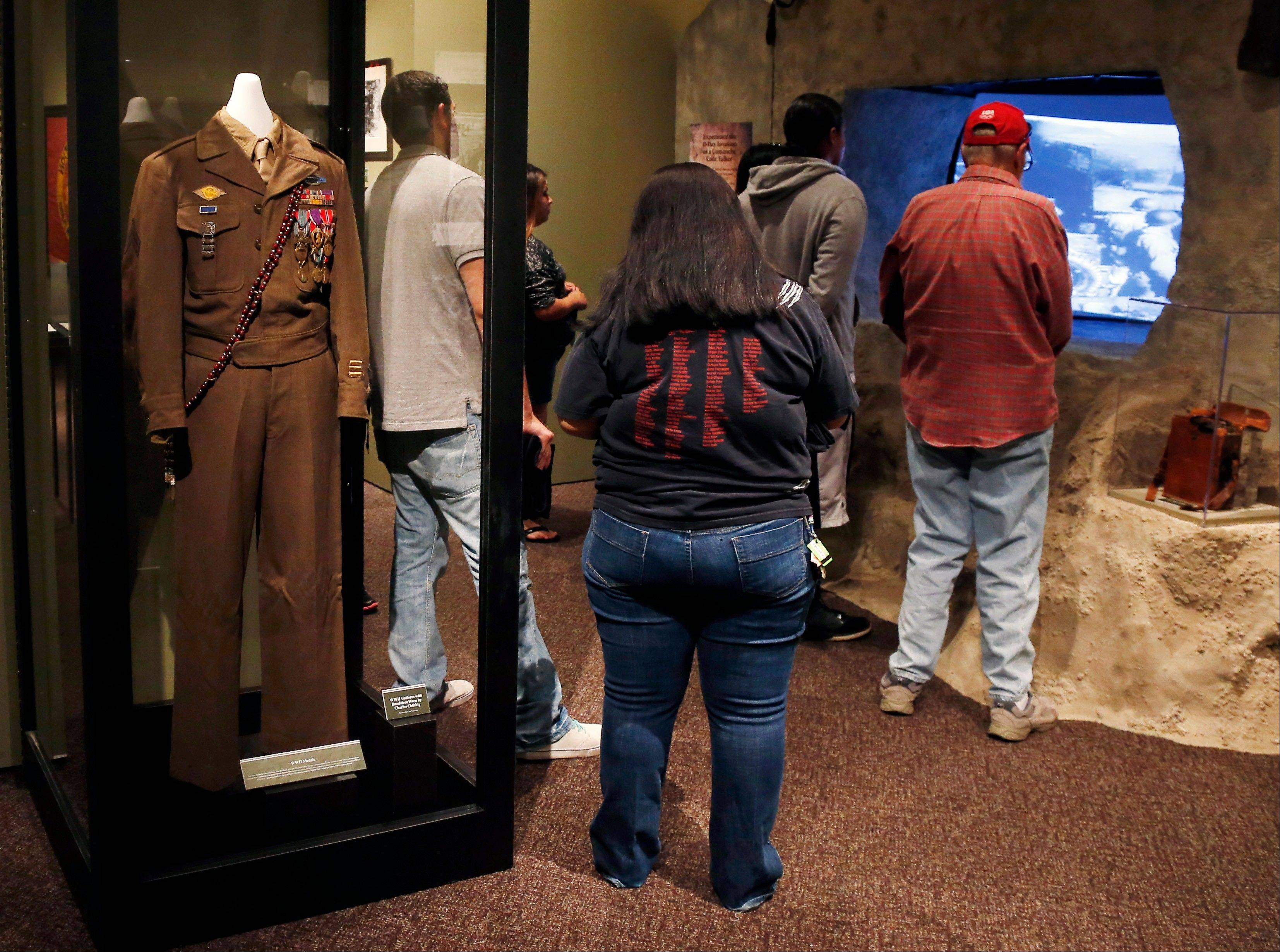 A World War II uniform with the bandolero worn by Comanche Code Talker Charles Chibbity is on display in an exhibit about the code takers at the Comanche National Museum and Cultural Center in Lawton, Okla. Visitors, right, watch a video on the D-Day invasion at Normandy.