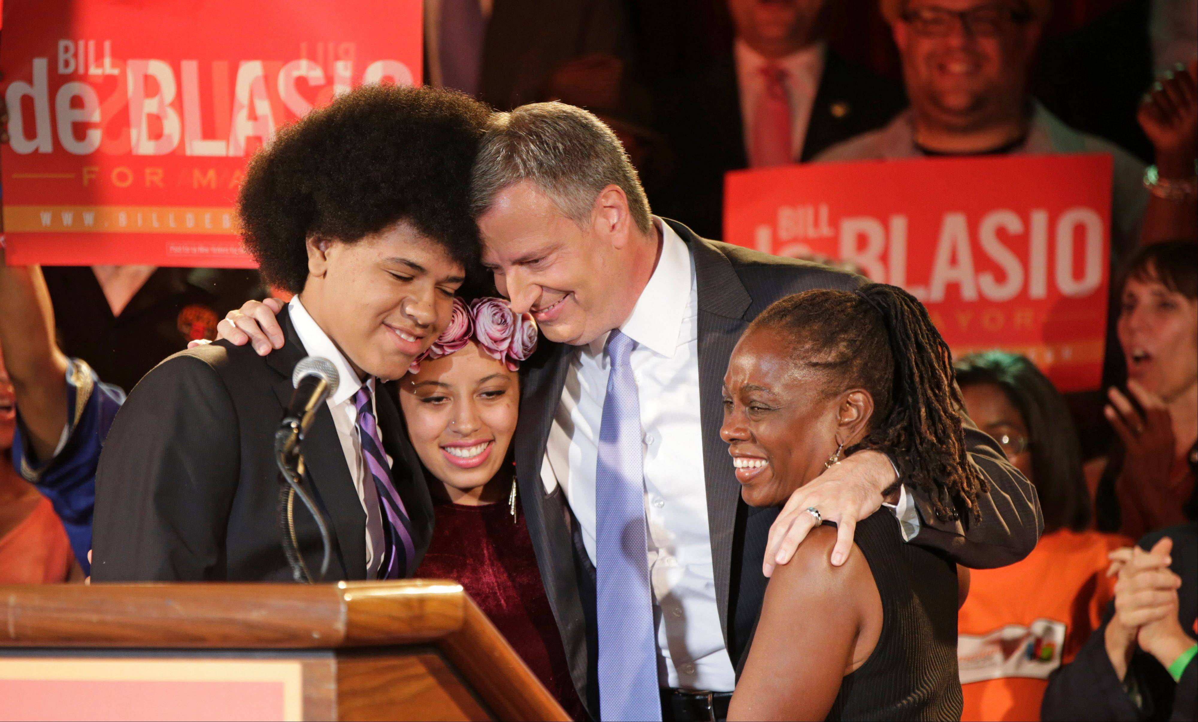 New York Democratic mayoral hopeful Bill de Blasio embraces his son Dante, left, daughter Chiara and wife Chirlane McCray at his election headquarters after polls closed in the city's primary election in New York. Dante, 16, whose large, perfectly coifed Afro is hard to miss at campaign stops and in a TV spot as his dad runs for New York City mayor. The dress code at his public high school in Brooklyn does not have a hair restriction.