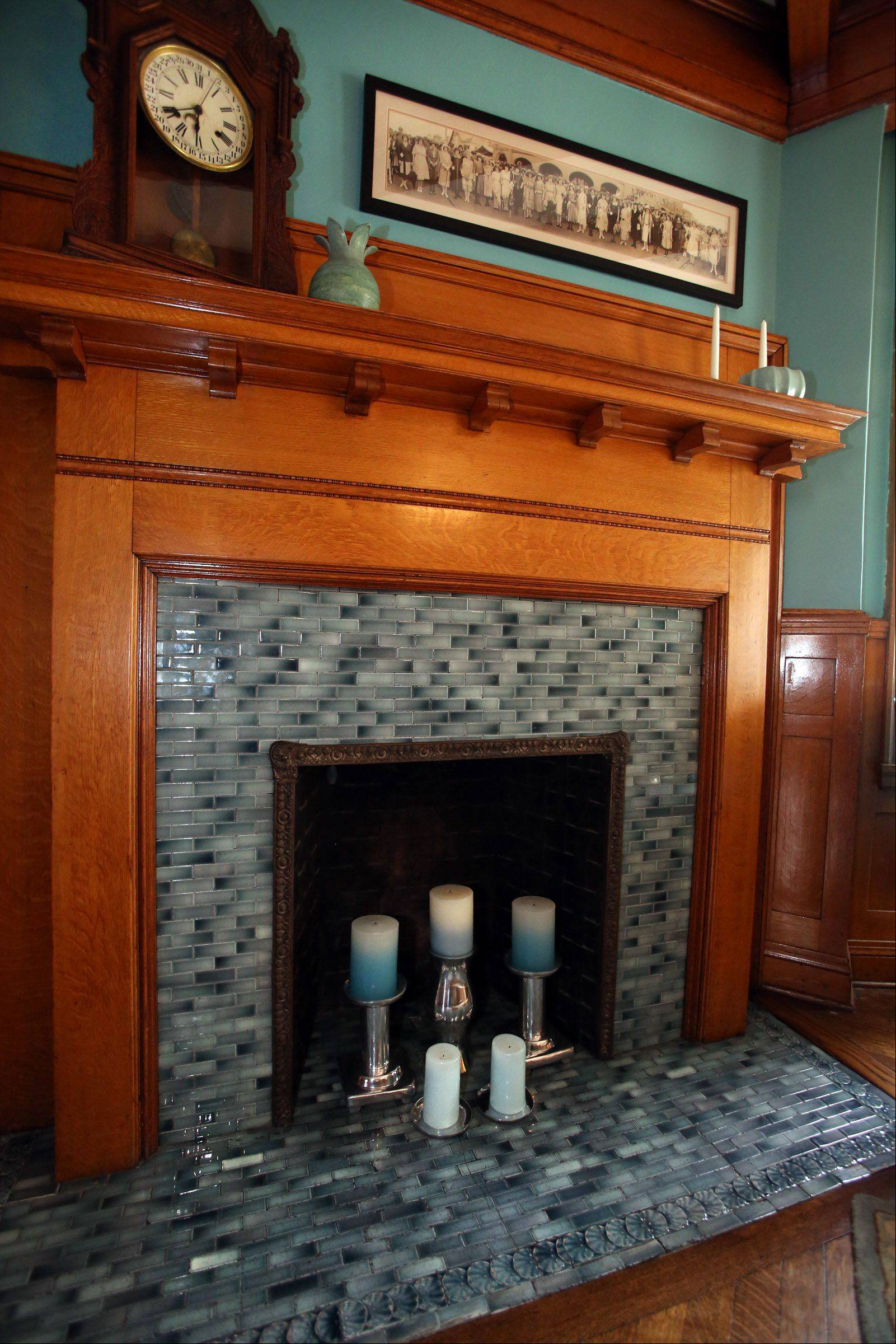 The fireplace in the Thompsons' dining room shows turquoise tiles, matched by the room's walls.