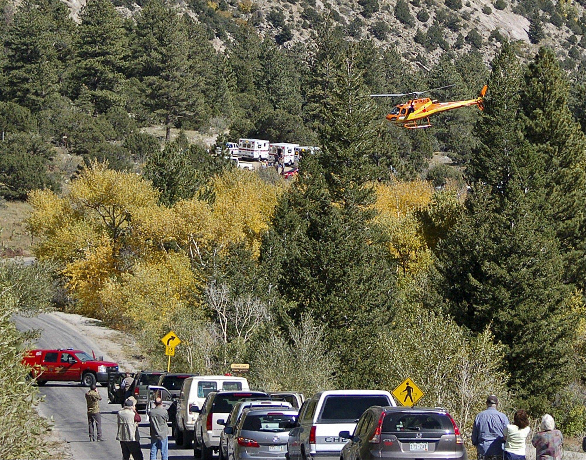 A Flight for Life Helicopter rises above backed-up traffic Monday in south-central Colorado after roads were closed to permit emergency personnel to get to hikers trapped by a rock slide.