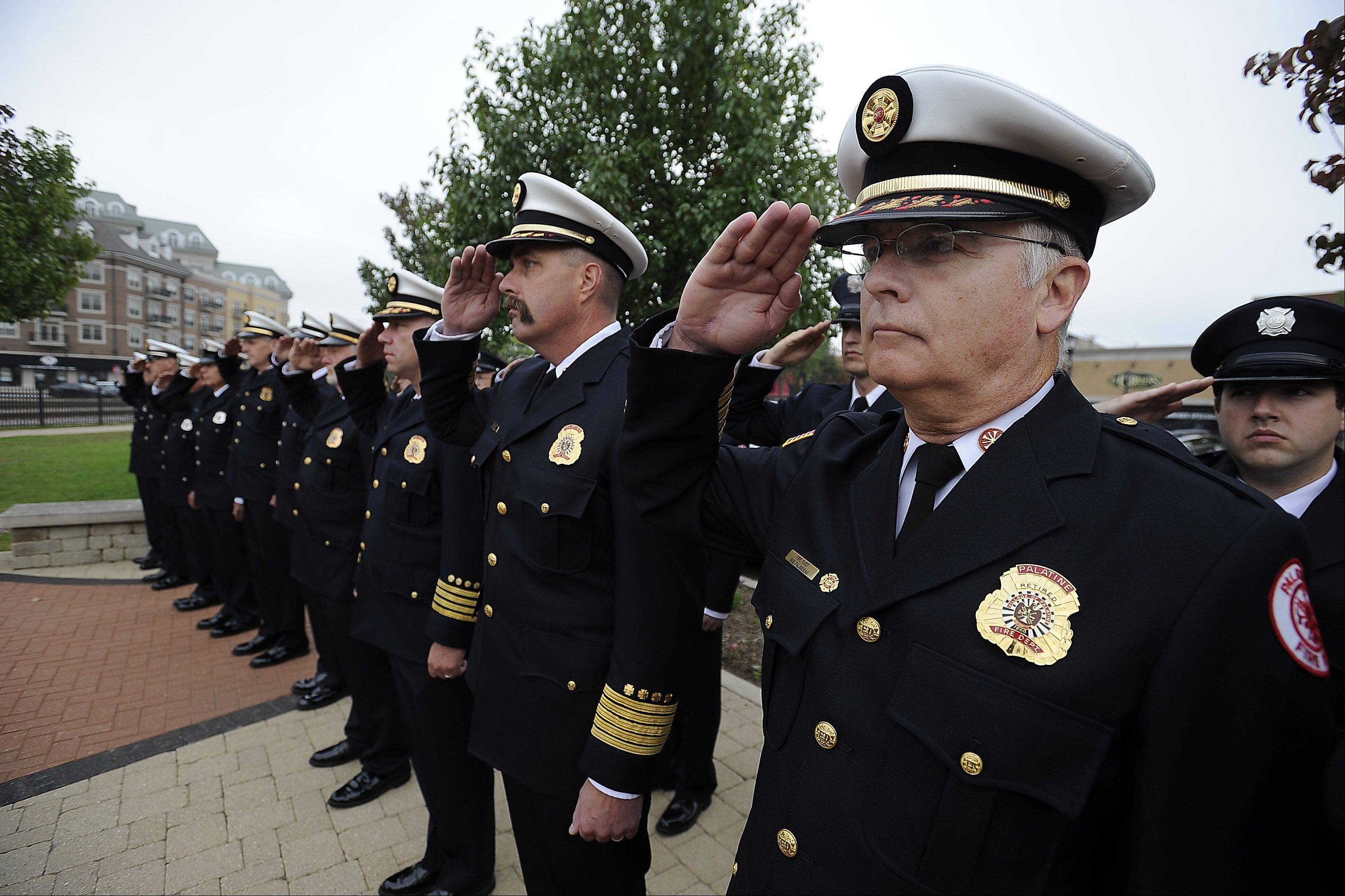 Retired Palatine firefighter Bob Falardeau (right) and Palatine Fire Chief Scott Andersen salute during a ceremony Tuesday morning at the Firefighter's Memorial in downtown Palatine. The ceremony honored two volunteer firefighters who died after a passenger train struck their fire truck Oct. 1, 1946.