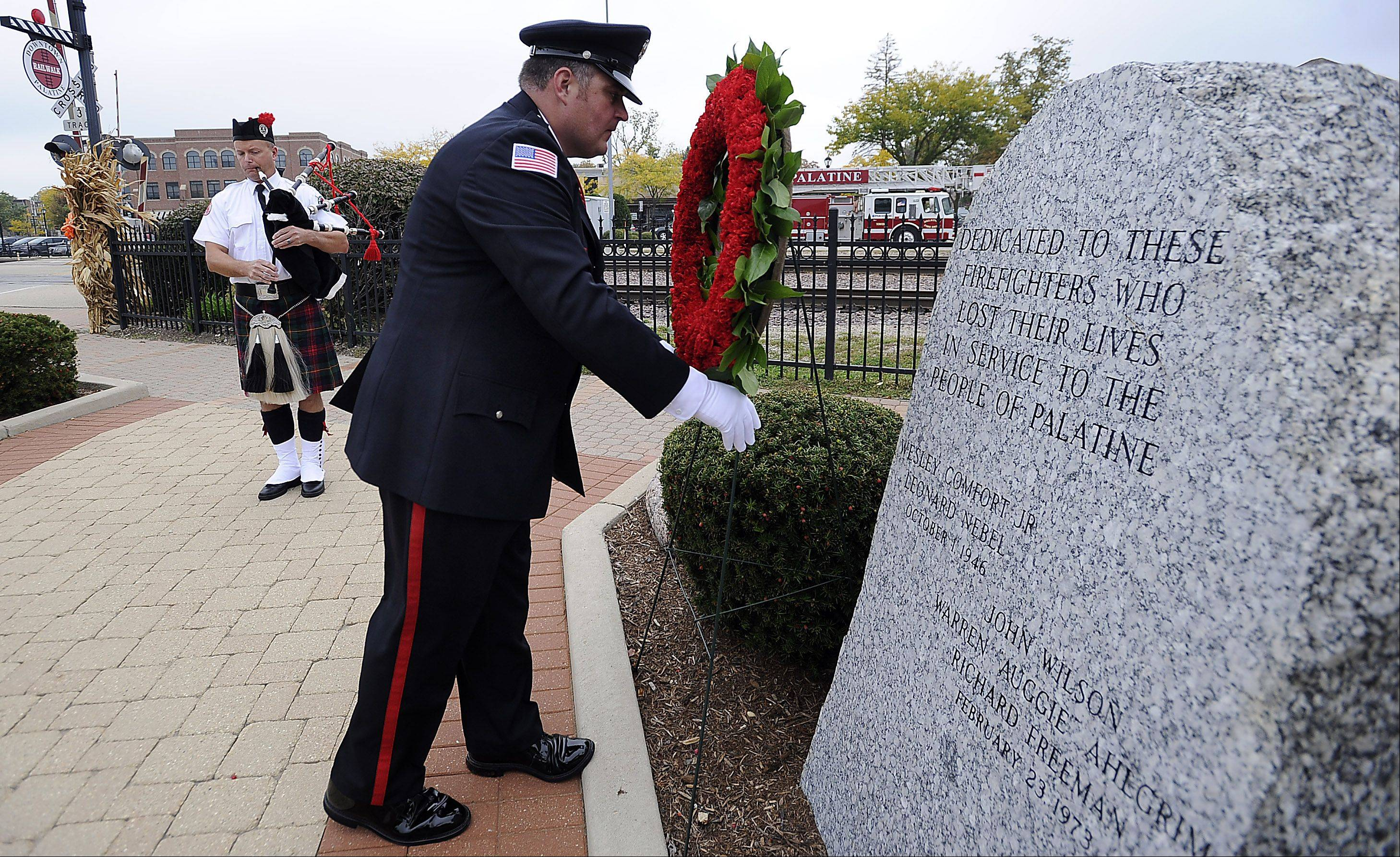 Palatine firefighter Dale Stankewicz lays a wreath during a ceremony Tuesday morning at the Firefighter's Memorial near the crossing where a passenger train struck a fire truck on Oct. 1, 1946.