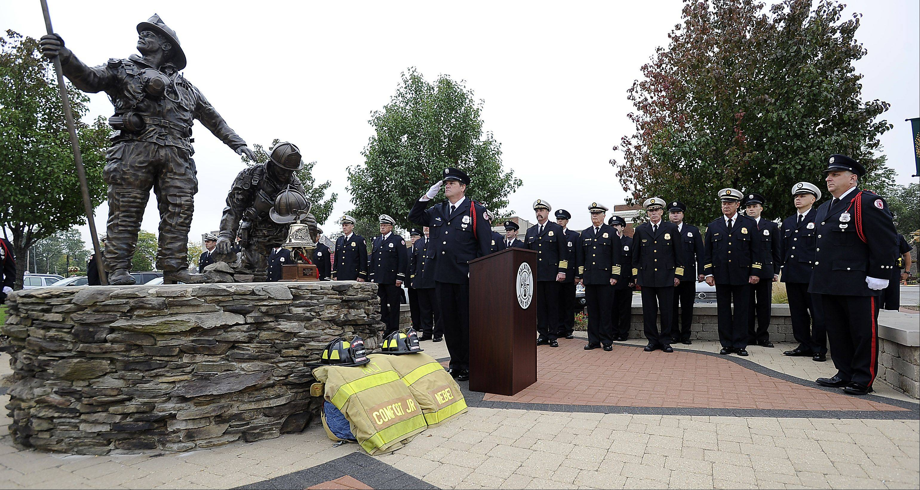 Retired Palatine firefighter/paramedic Mark Hallett salutes during a ceremony Tuesday morning at the Firefighter's Memorial near the railroad crossing in downtown Palatine where a passenger train struck a fire truck on Oct. 1, 1946.