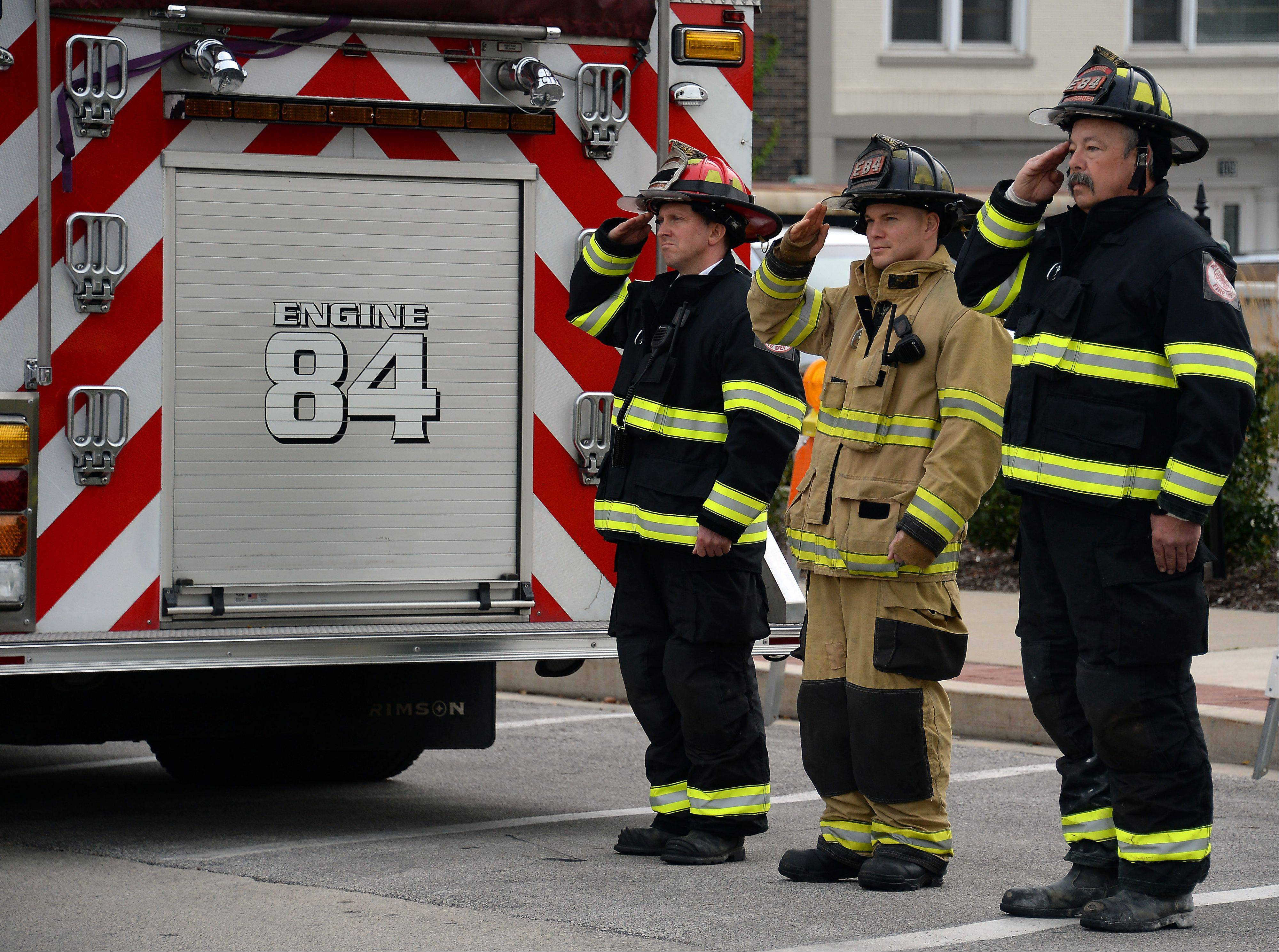 Palatine firefighters Lt. Scott Meservey, Chris Meuret and Jim Samack stand at attention during a ceremony Tuesday morning at the Firefighter's Memorial in downtown Palatine to honor two volunteer firefighters who died after a passenger train struck their fire truck Oct. 1, 1946.