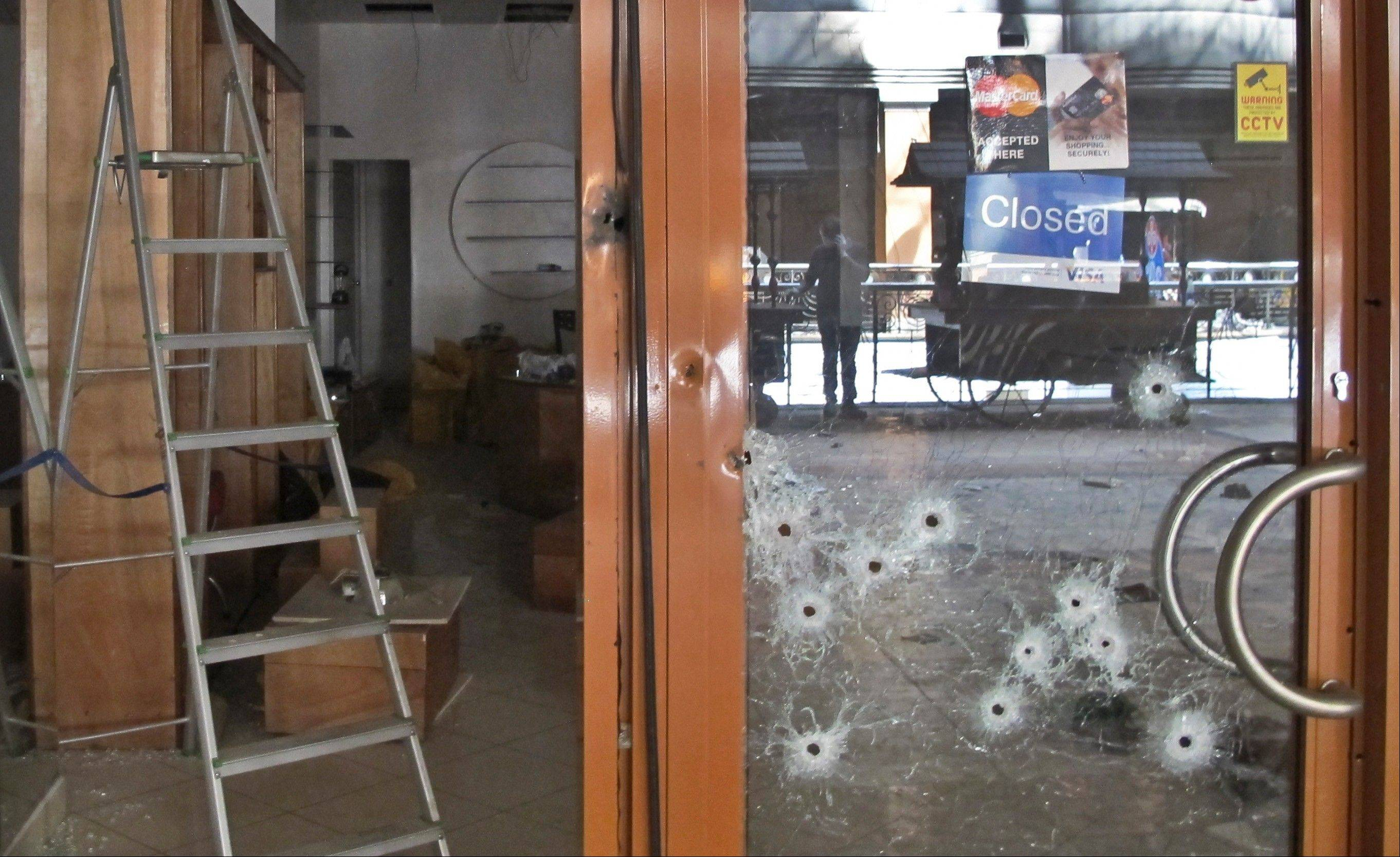 Bullet-holes pepper the glass door of a shop in the Westgate Mall in Nairobi, Kenya Tuesday, Oct. 1, 2013. Kenyan President Uhuru Kenyatta says Kenya will keep its troops in Somalia to help that country's beleaguered government battle the armed Islamic extremist group al-Shabab, which attacked the mall in Nairobi on Sept. 21 claiming at least 67 lives.