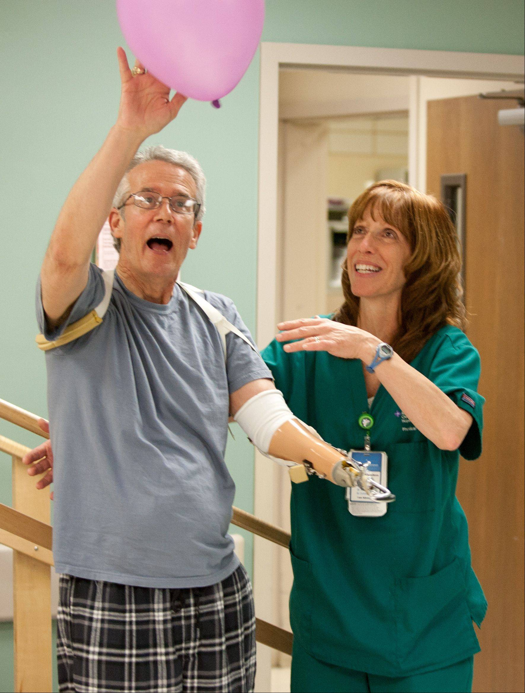Working with physical therapy assistant Kathleen Dub during rehab at the Advocate Christ Medical Center in Oak Lawn, Kent Carson learned how to use the hook at the end of his left arm to grab objects. Now Carson hopes to persuade his insurance company to pay for a bionic hand with movable fingers.